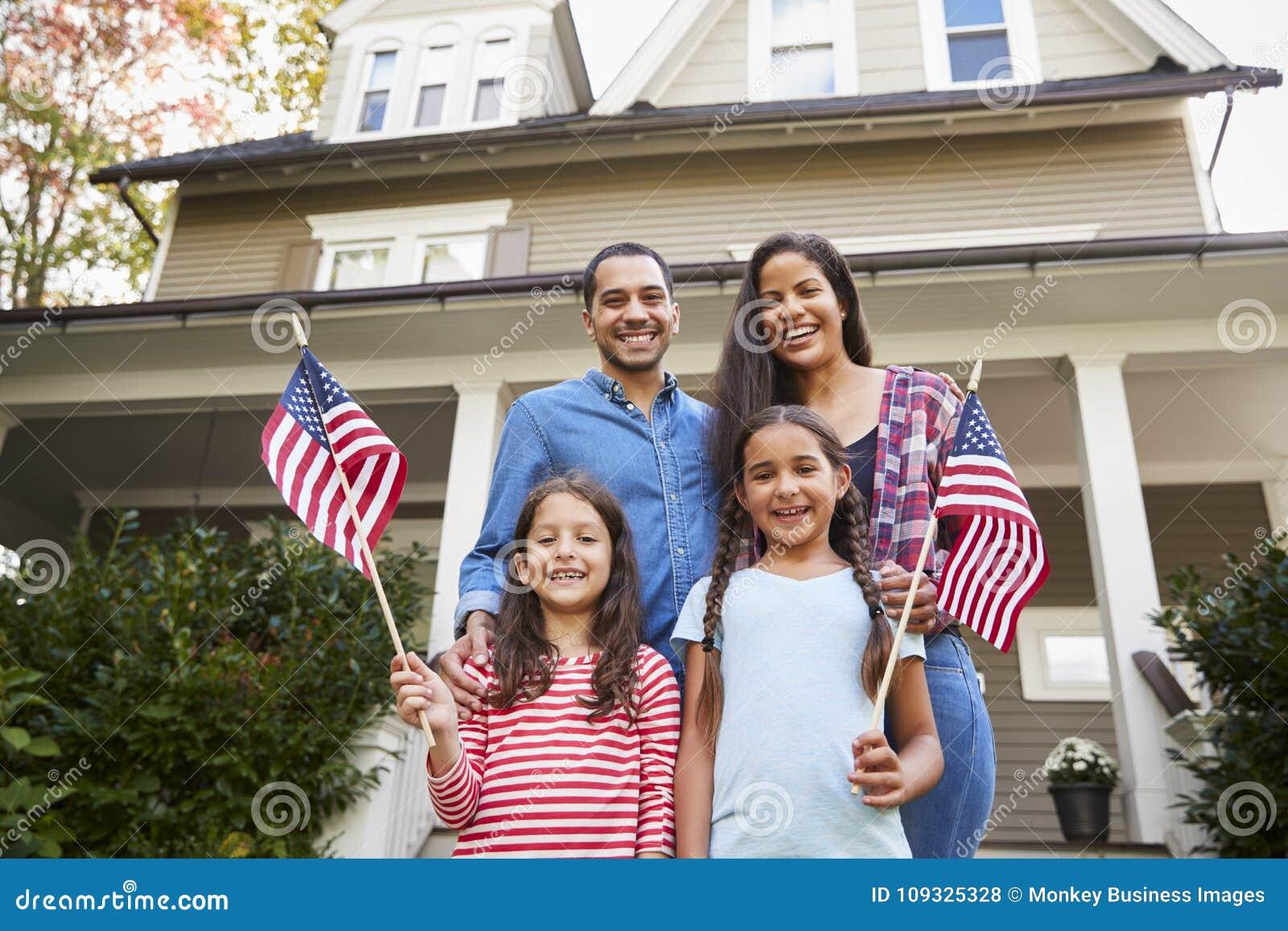 Πορτρέτο της οικογένειας έξω από τις αμερικανικές σημαίες εκμετάλλευσης σπιτιών