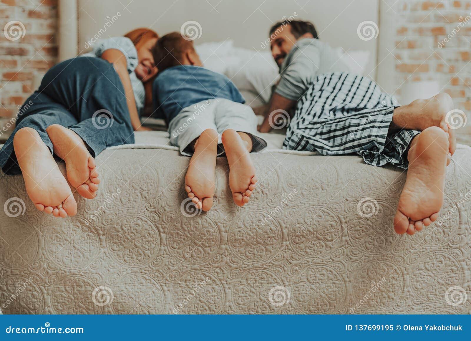 Πορτρέτο της οικογένειας τρία ζευγάρια των ποδιών στο κρεβάτι