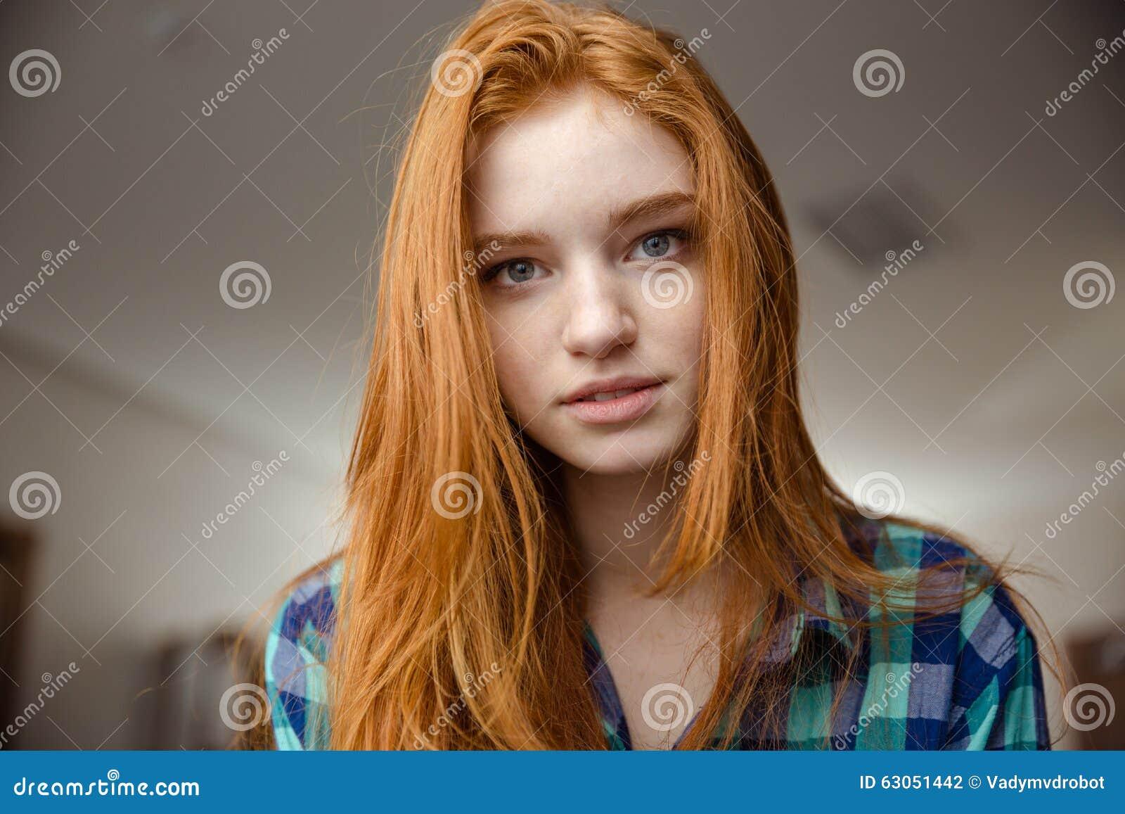 Πορτρέτο της στοχαστικής ελκυστικής redhead νέας γυναίκας στο πουκάμισο καρό