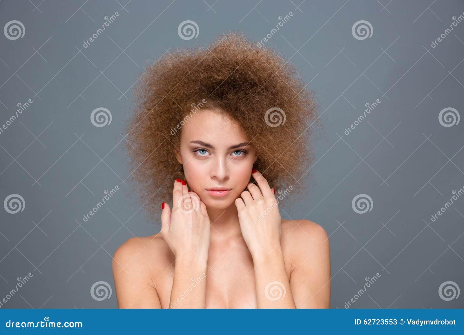 Πορτρέτο της τρυφερής φυσικής γυναίκας με το ογκώδες σγουρό hairstyle