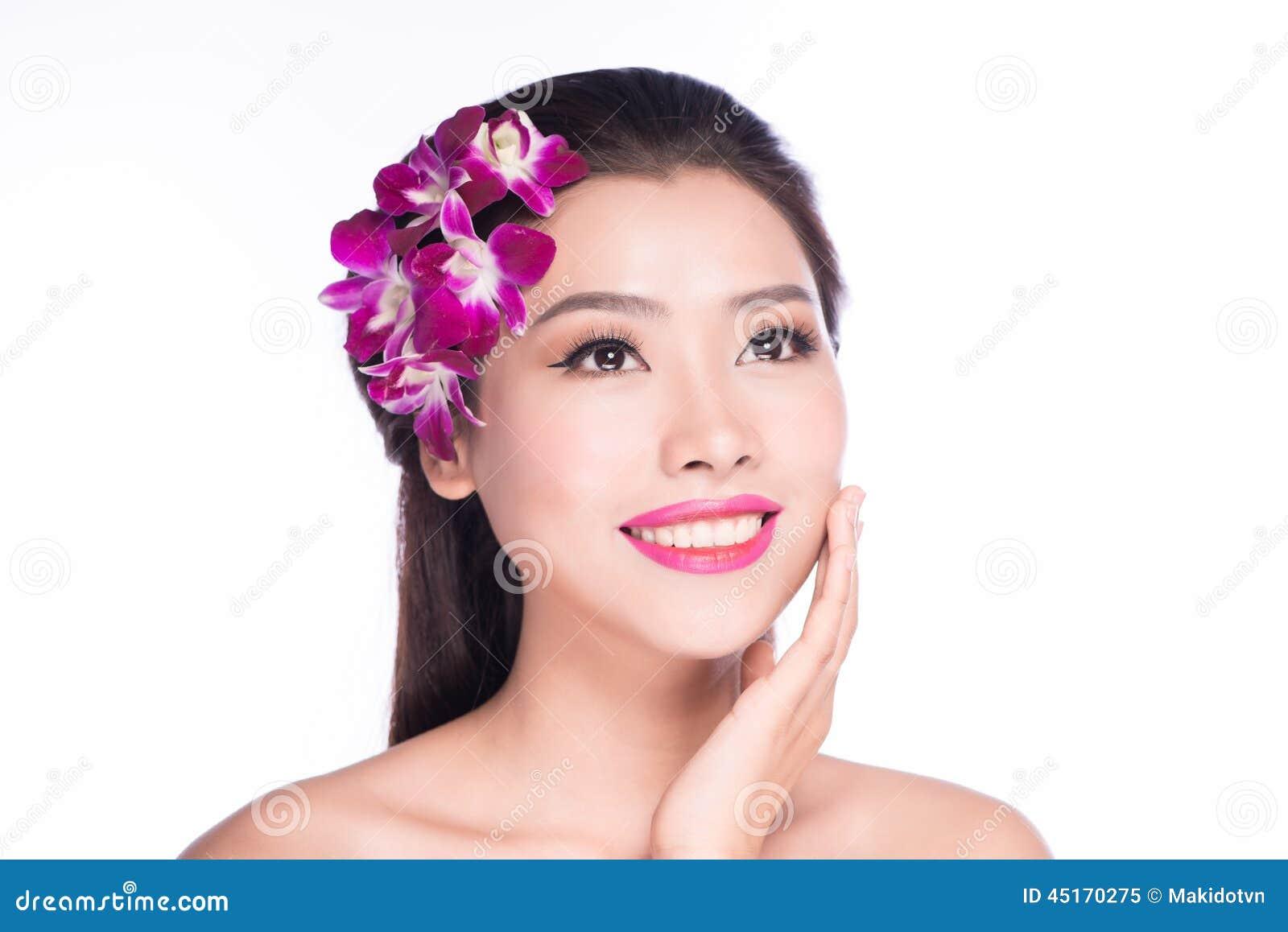 Πορτρέτο της όμορφης γυναίκας με το λουλούδι ορχιδεών στην τρίχα της Τέλειο δέρμα τέλειο δέρμα να ισχύσει σχολιάζει το χείλι κάνε