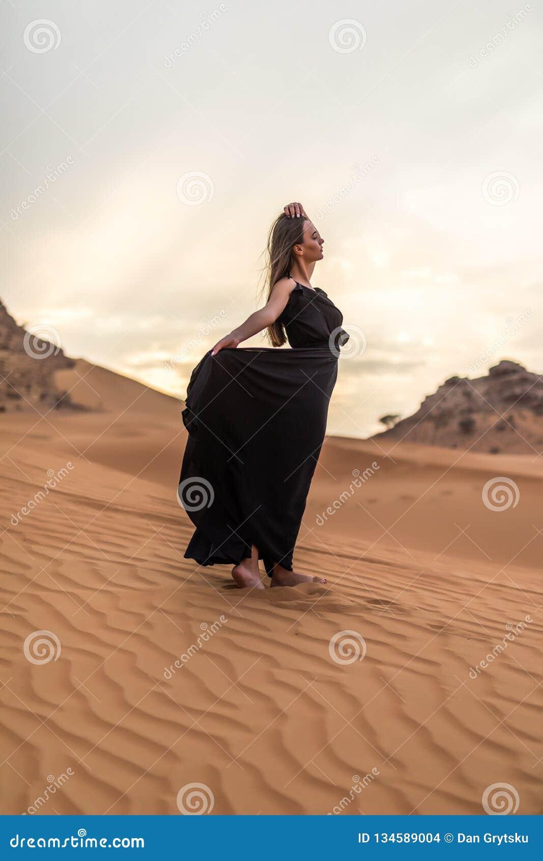 Πορτρέτο της όμορφης νέας γυναίκας τοποθέτηση φορεμάτων πολύ κυματισμού στη μαύρη υπαίθρια στην αμμώδη έρημο