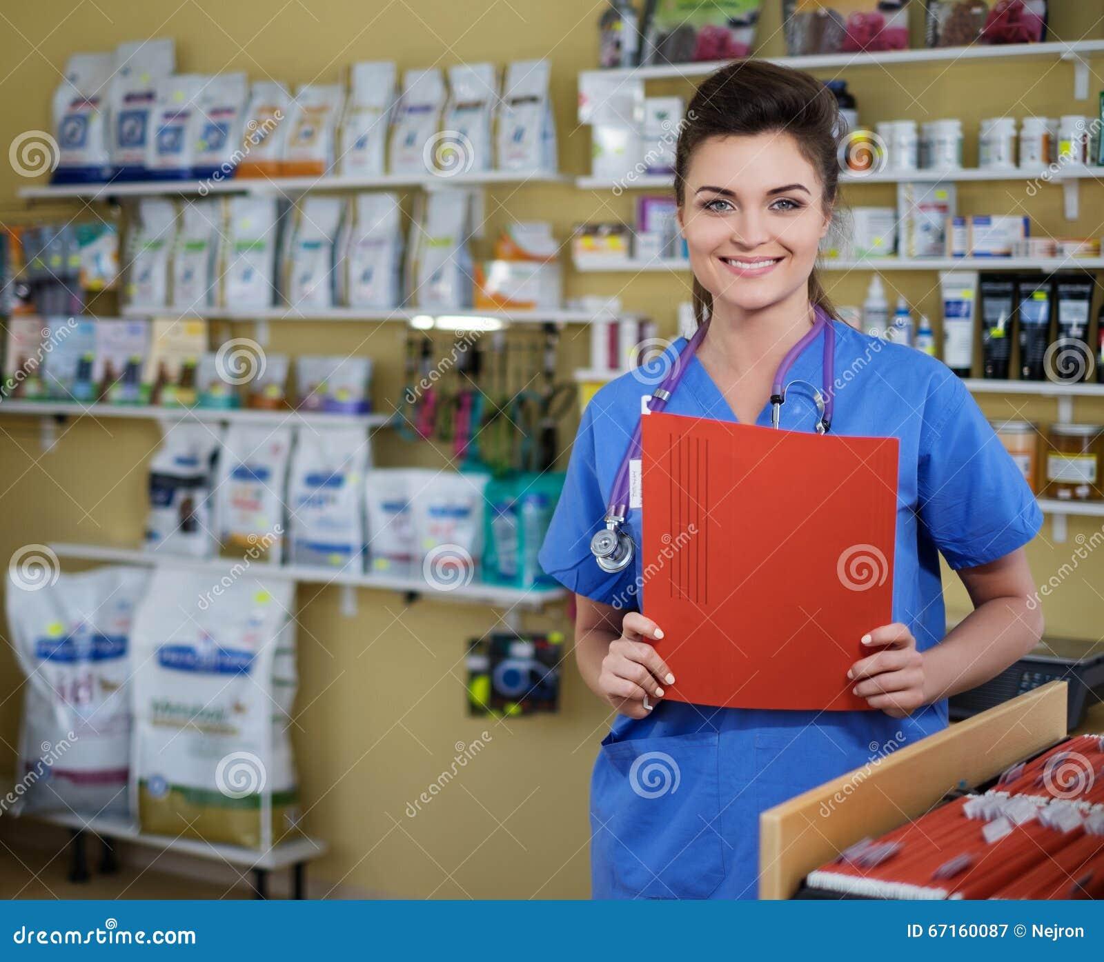 Πορτρέτο της όμορφης νοσοκόμας με το φάκελλο στην κλινική κτηνιάτρων