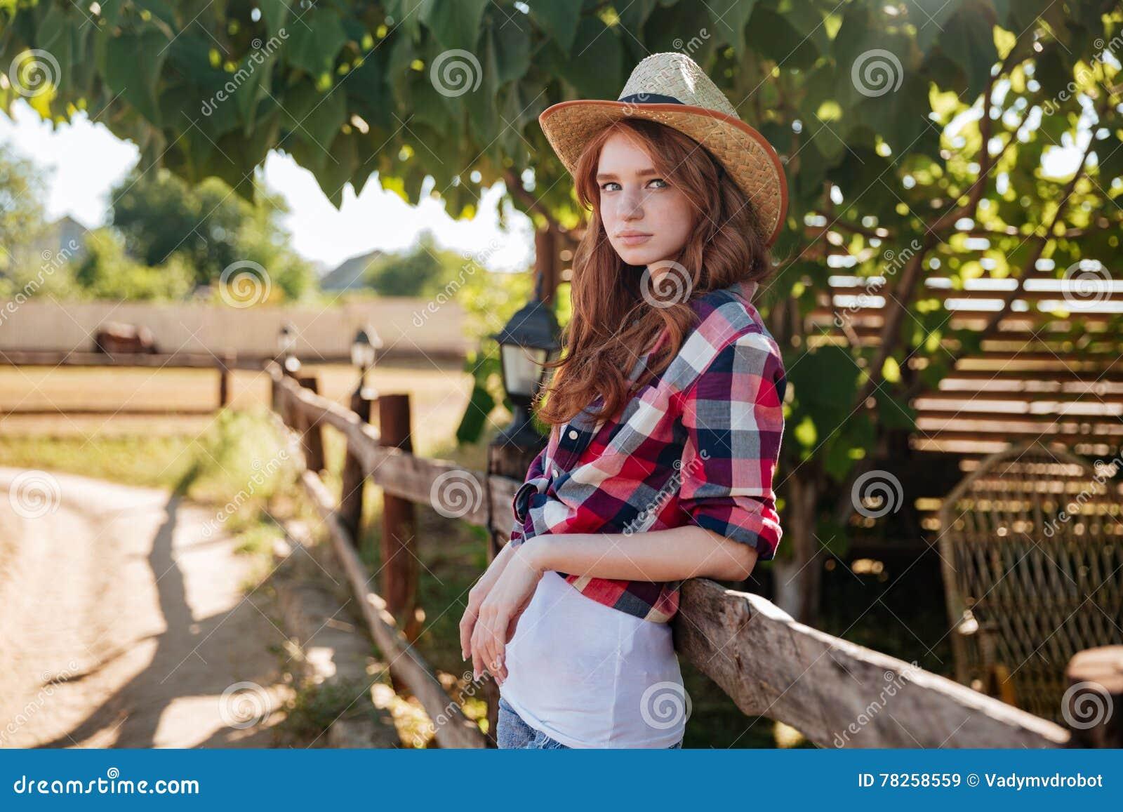 Πορτρέτο του αρκετά redhead cowgirl που κλίνει στο φράκτη αγροκτημάτων