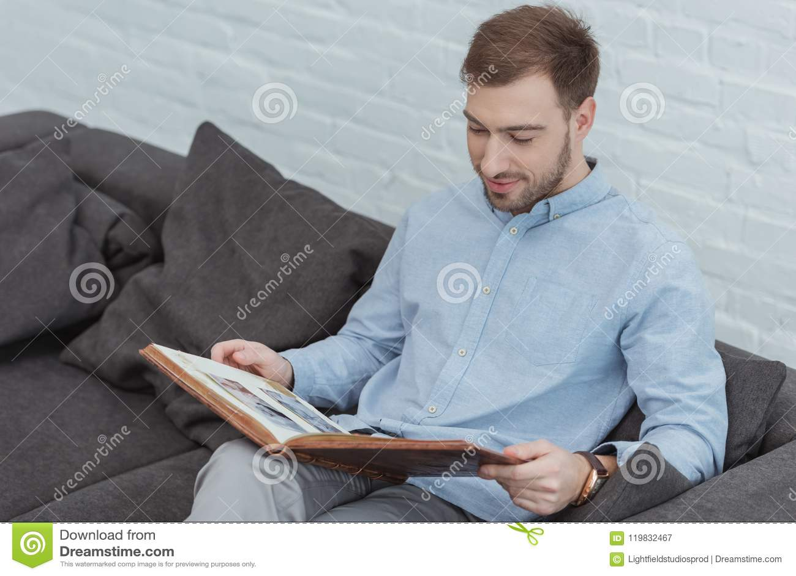 πορτρέτο του ατόμου που εξετάζει τις φωτογραφίες στο λεύκωμα φωτογραφιών στηργμένος στον καναπέ