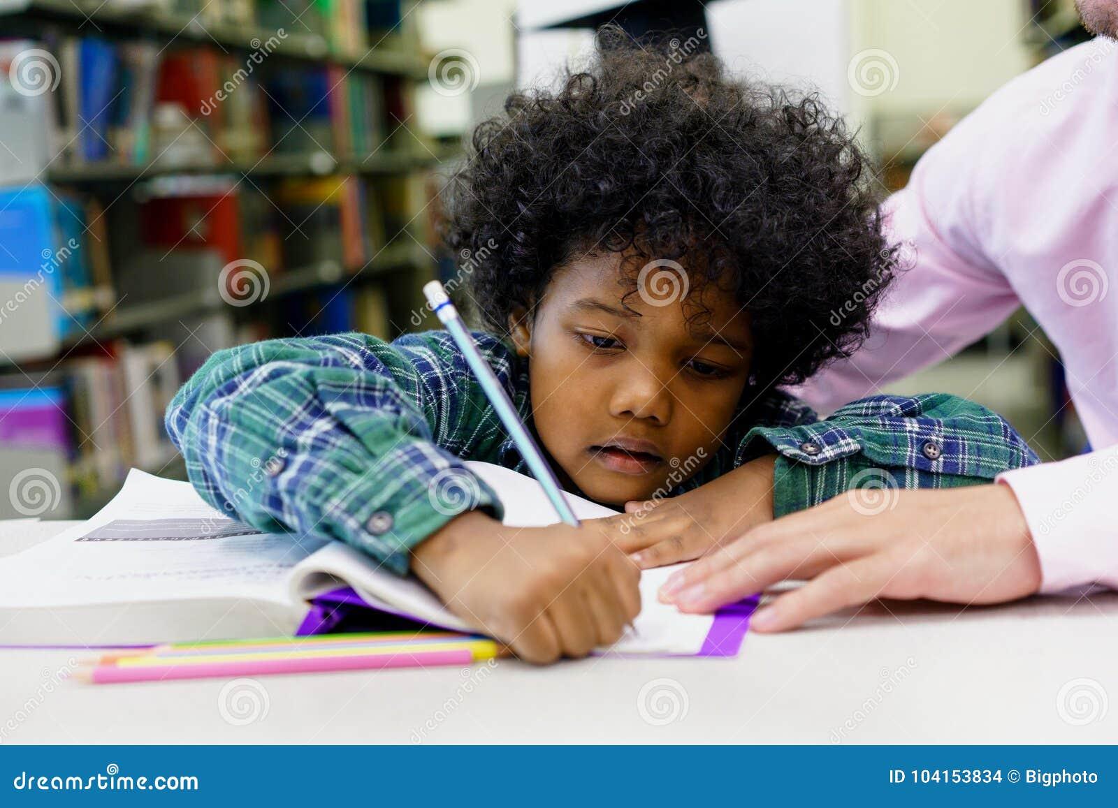 Πορτρέτο του βοηθώντας μικρού παιδιού δασκάλων με την εργασία στο λι
