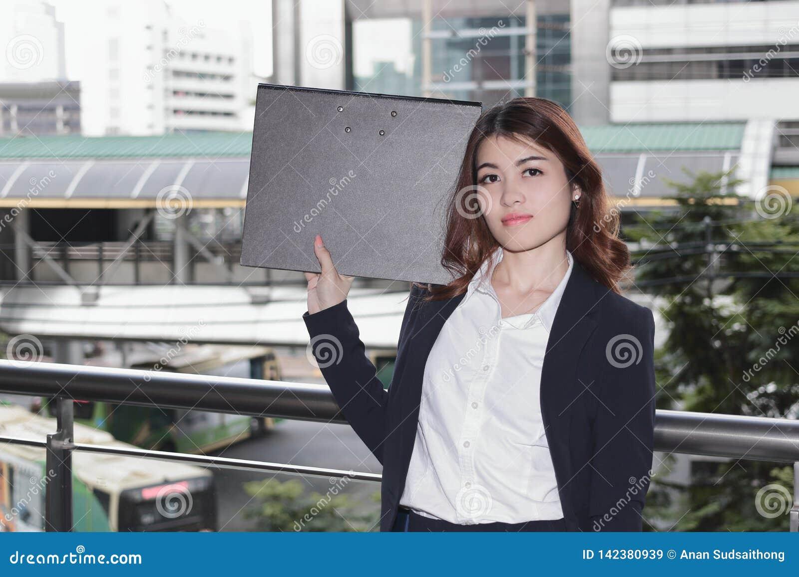 Πορτρέτο του ελκυστικού νέου ασιατικού φακέλλου εγγράφων εκμετάλλευσης γυναικών γραμματέων στο εξωτερικό γραφείο