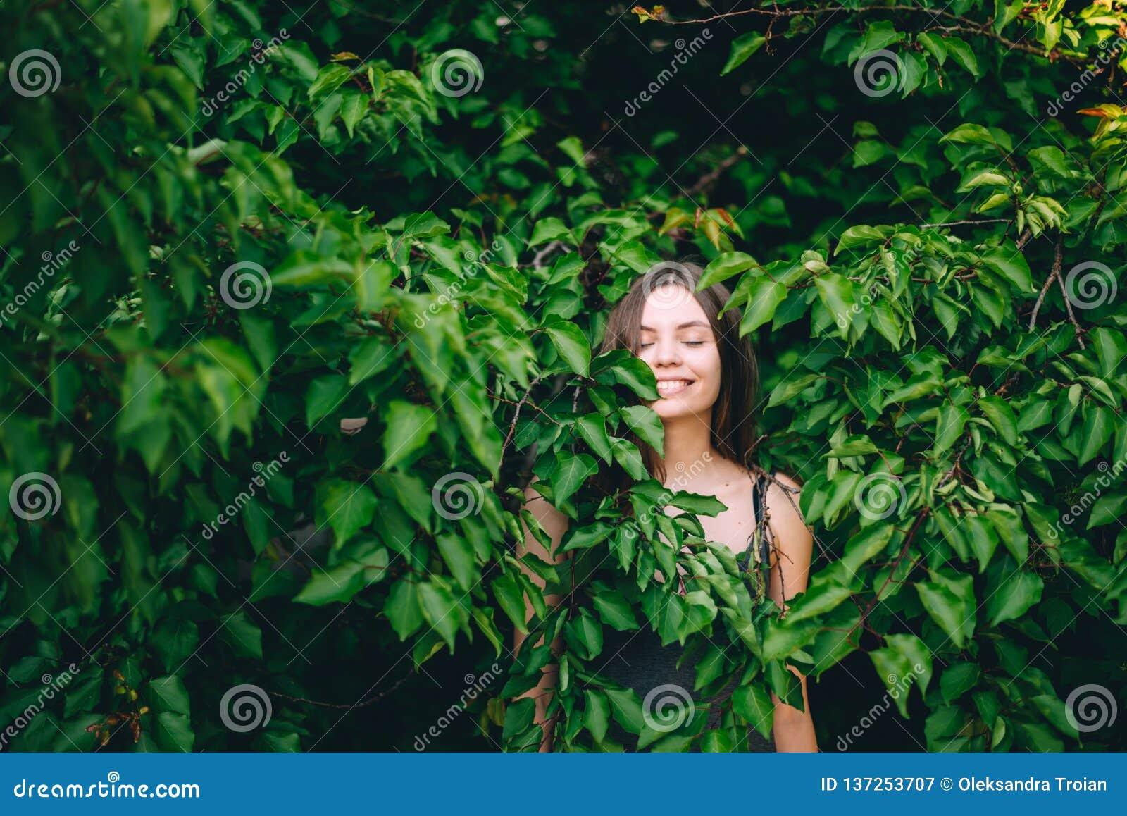 Πορτρέτο του ευτυχούς αρκετά νέου κοριτσιού εφήβων στα πράσινα φύλλα που χαμογελά υγιή φυσικό