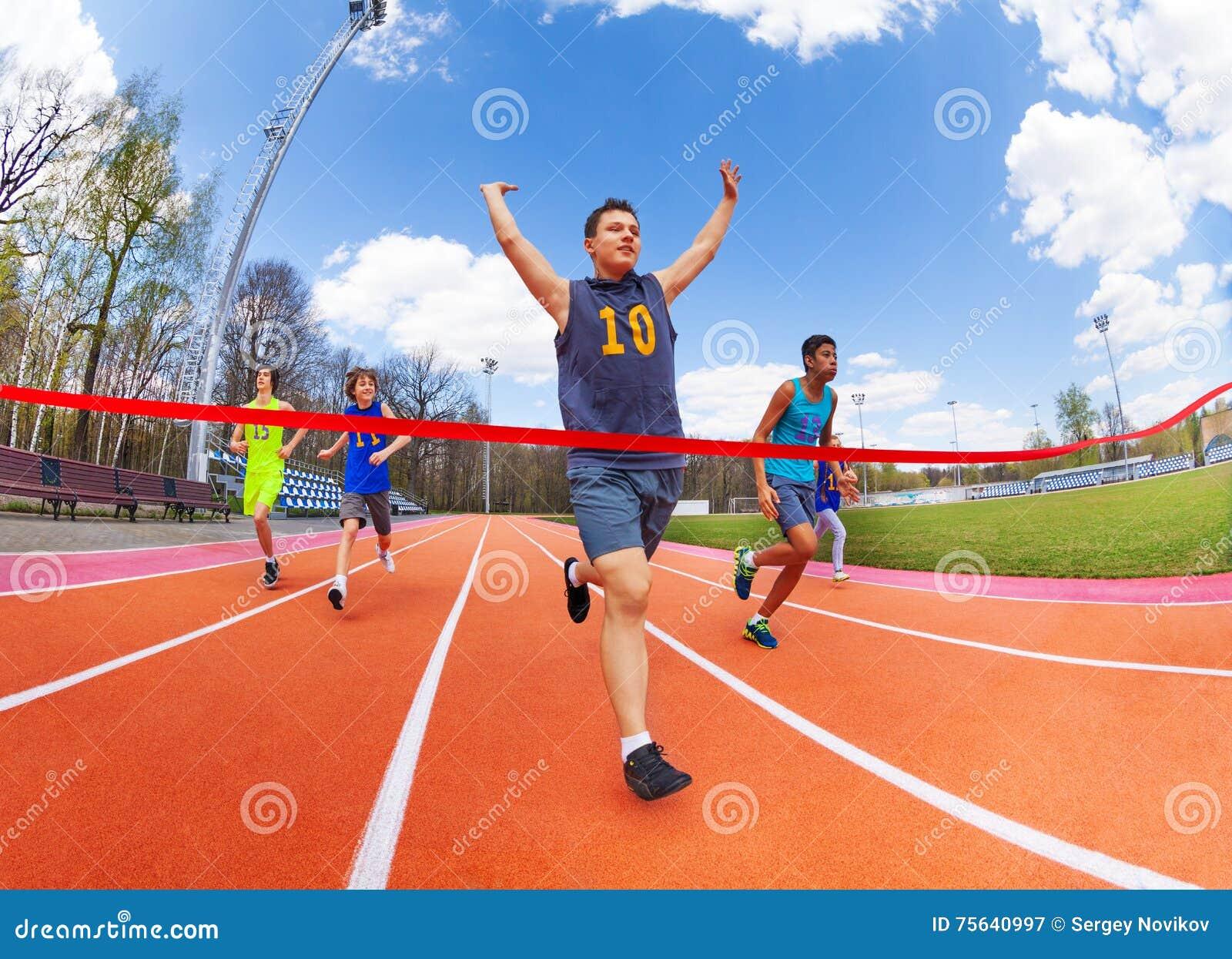 Πορτρέτο του εφηβικού sprinter που διασχίζει τη γραμμή τερματισμού