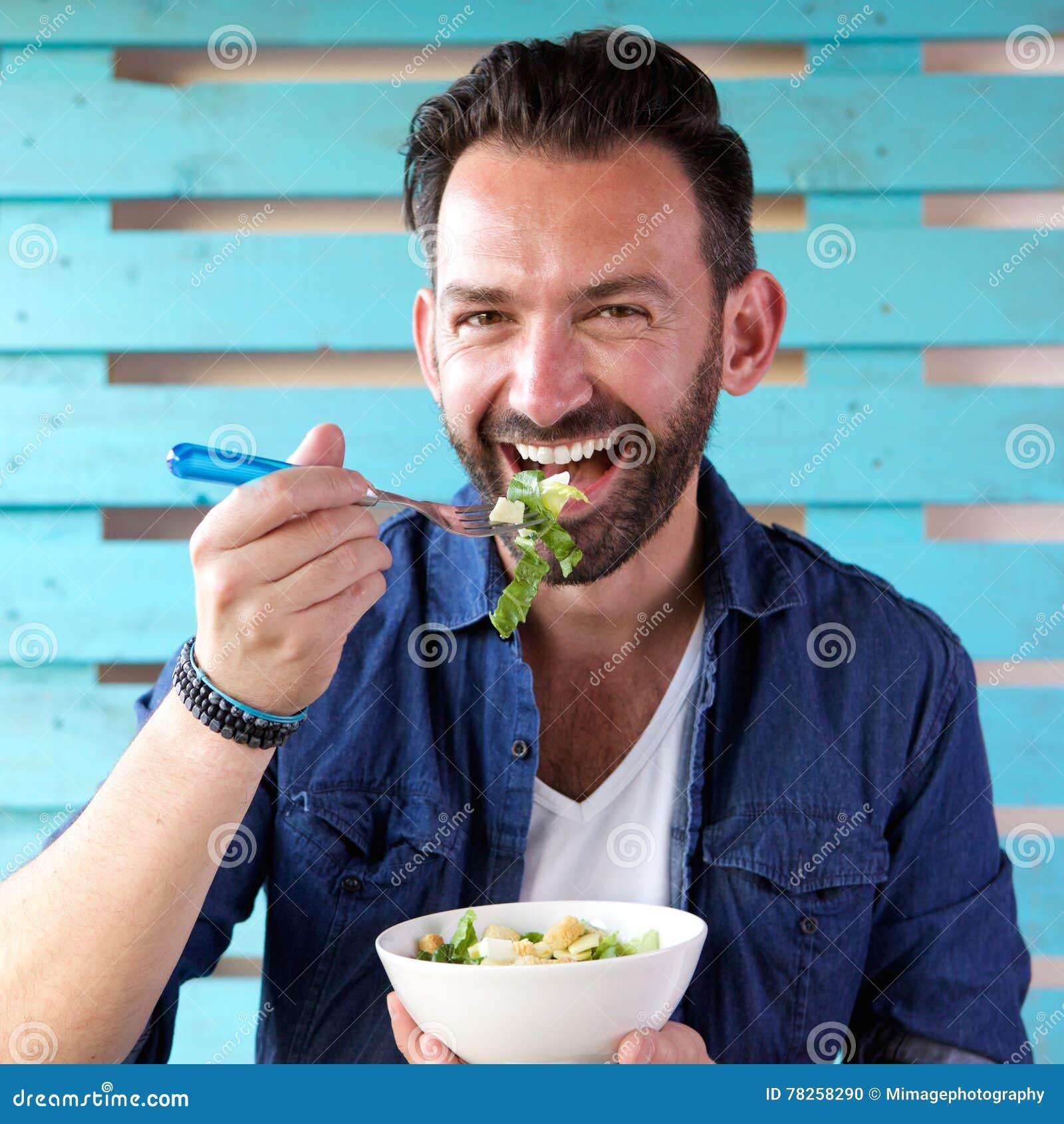 Πορτρέτο του εύθυμου ατόμου που τρώει τη σαλάτα