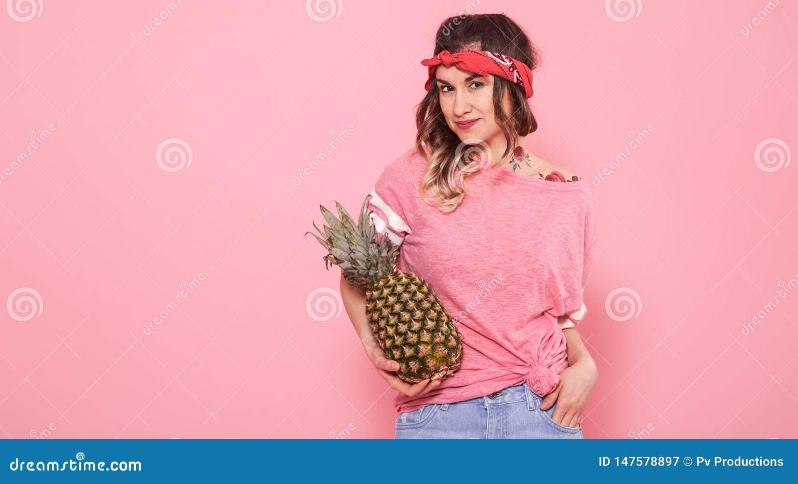 Πορτρέτο του κοριτσιού και του ανανά hipster που απομονώνονται στο ρόδινο υπόβαθρο