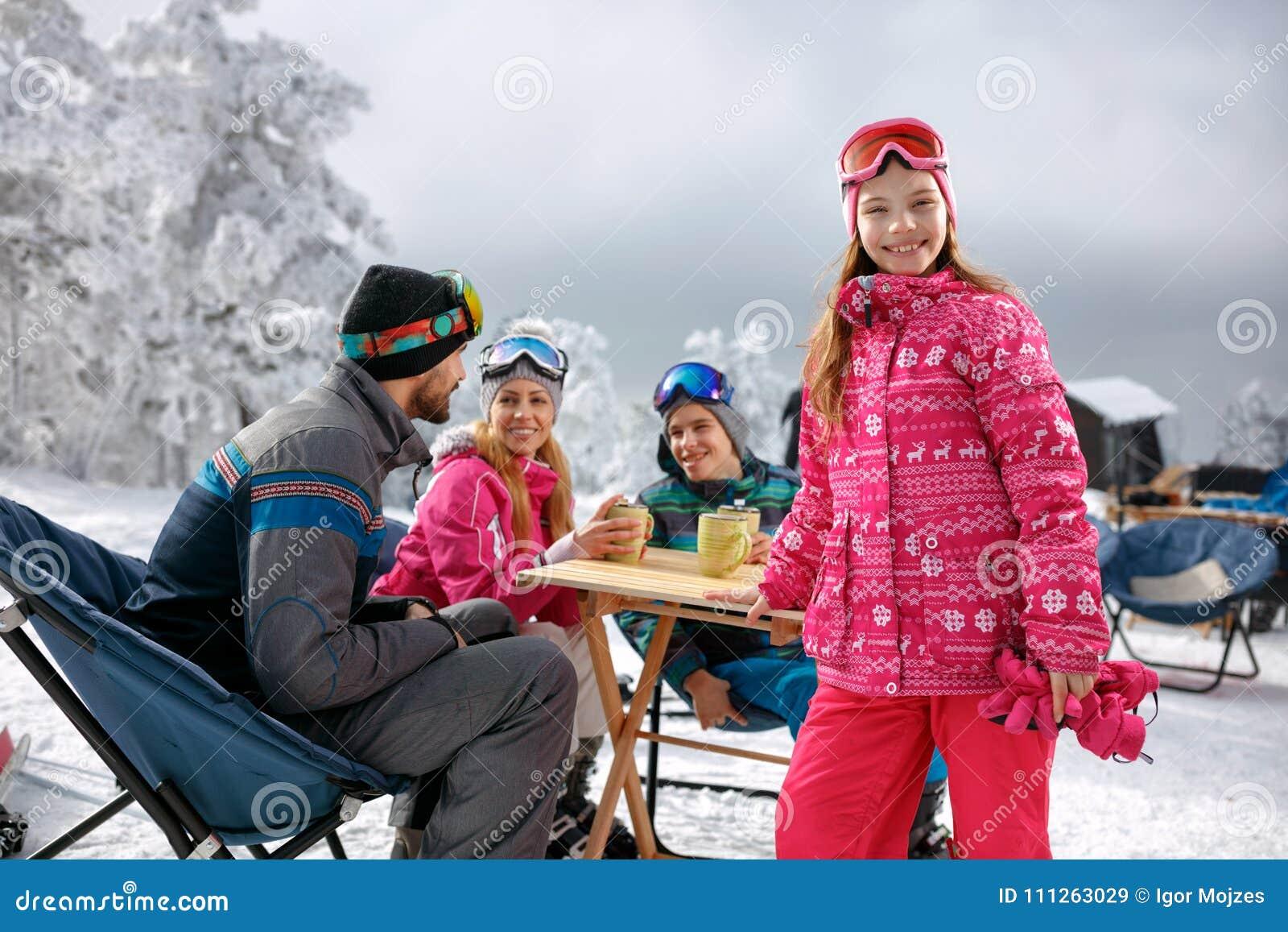 Πορτρέτο του κοριτσιού με την οικογένεια που απολαμβάνει τις χειμερινές διακοπές στο χιόνι