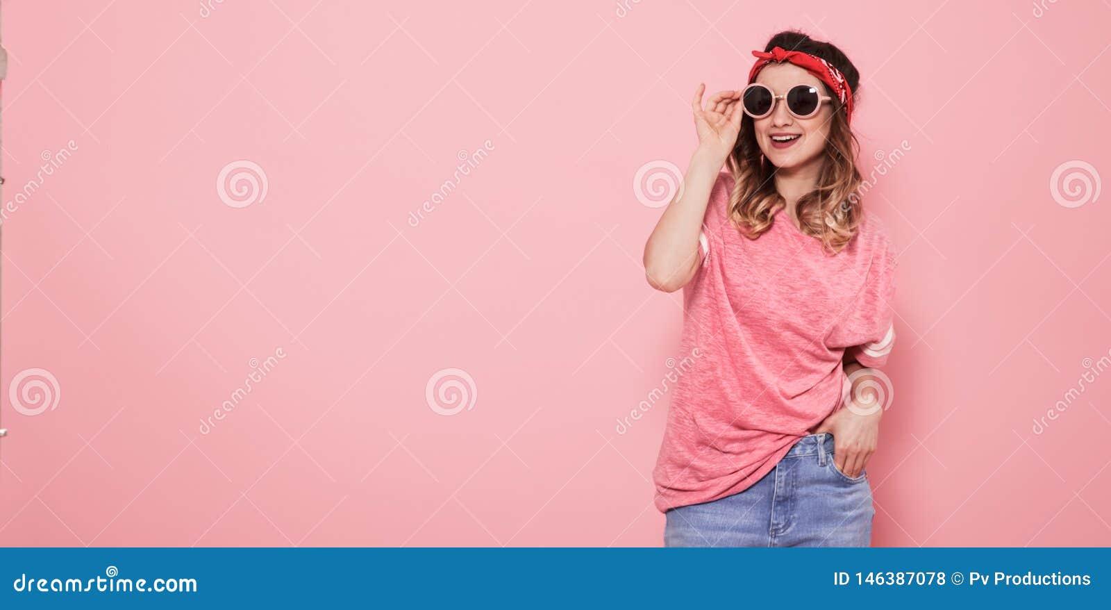 Πορτρέτο του κοριτσιού hipster στα γυαλιά στο ρόδινο υπόβαθρο