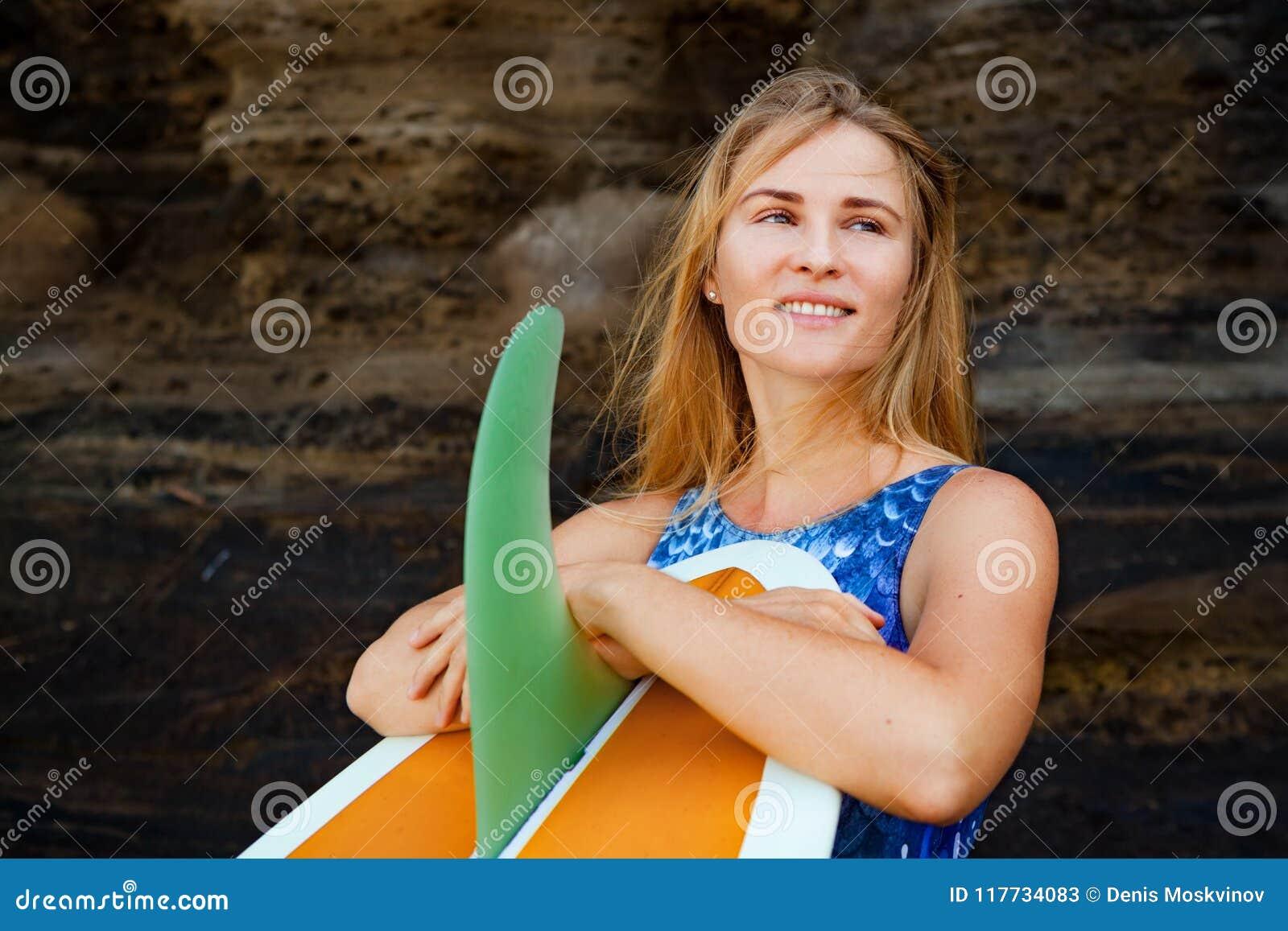 Πορτρέτο του κοριτσιού surfer με την ιστιοσανίδα στο υπόβαθρο απότομων βράχων θάλασσας