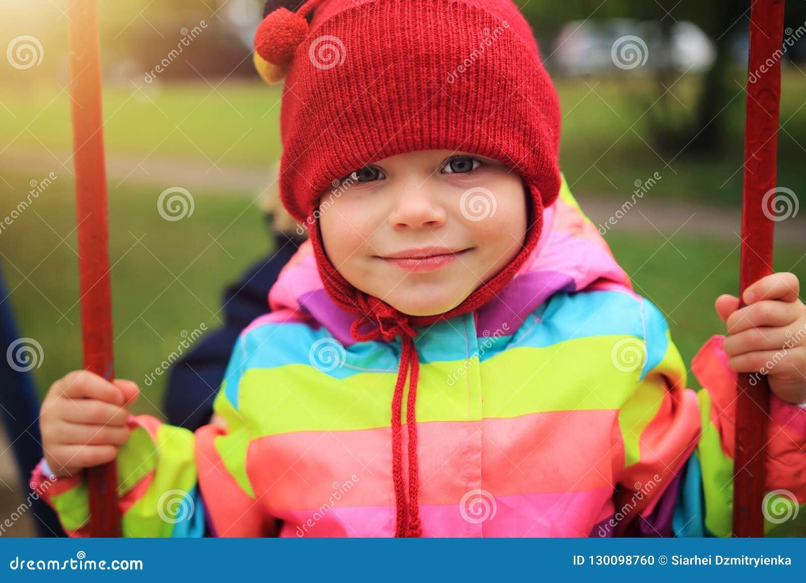 Πορτρέτο του μικρού κοριτσιού στην ταλάντευση Παιδιά που οδηγούν στο ιπποδρόμιο παιδική χαρά κατσικιών