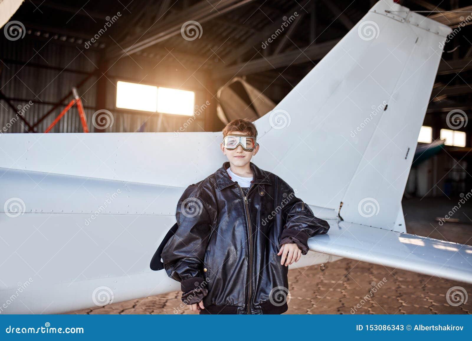 Πορτρέτο του μικρού παιδιού που στέκεται εκτός από την ελαφριά άσπρη ουρά αεροπλάνων μέσα στο υπόστεγο αεροσκαφών
