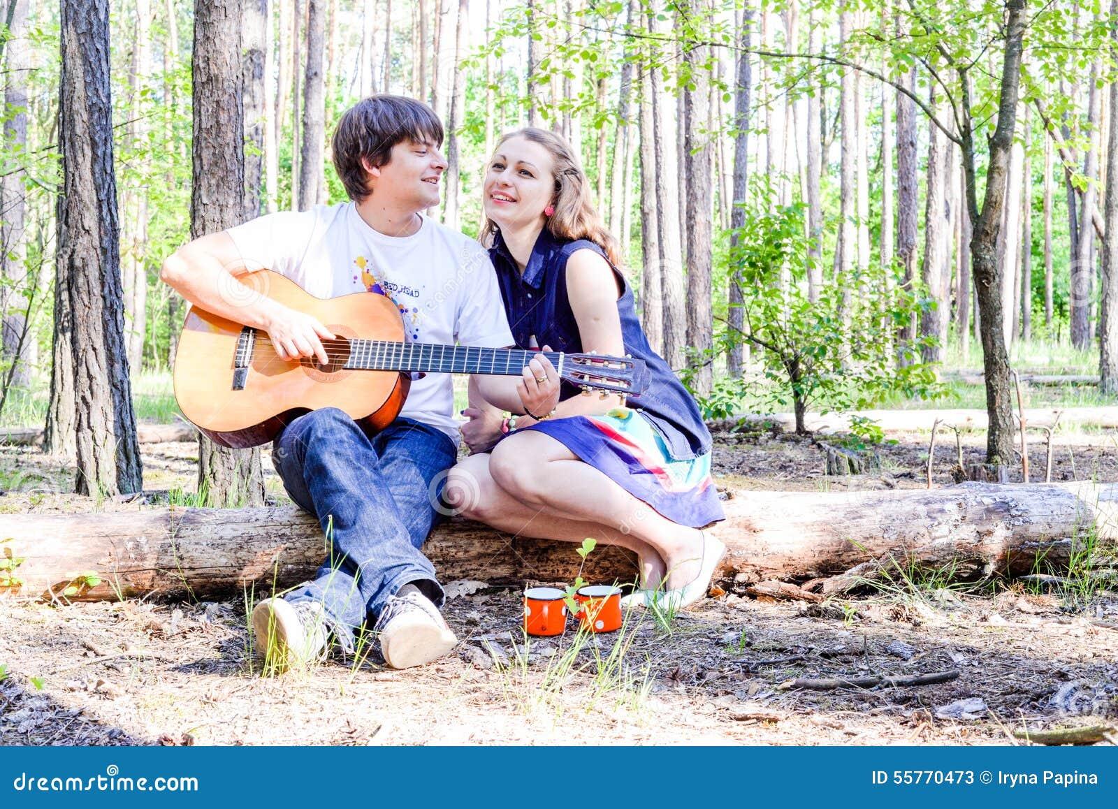 Πορτρέτο του νέου αγαπώντας ευτυχούς ζεύγους με την κιθάρα στο δάσος