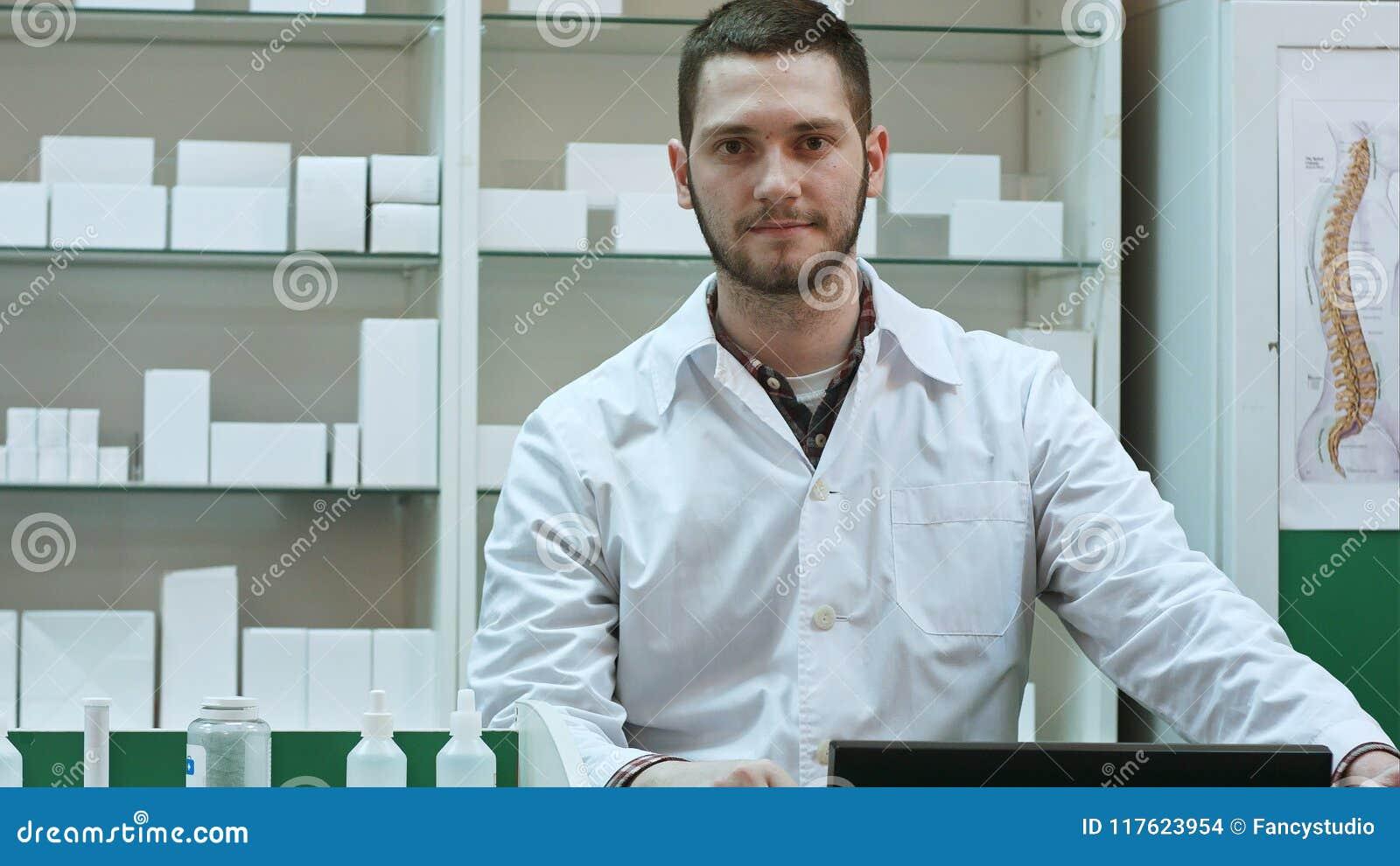 Πορτρέτο του νέου αρσενικού φαρμακοποιού που εξετάζει τη κάμερα και το χαμόγελο