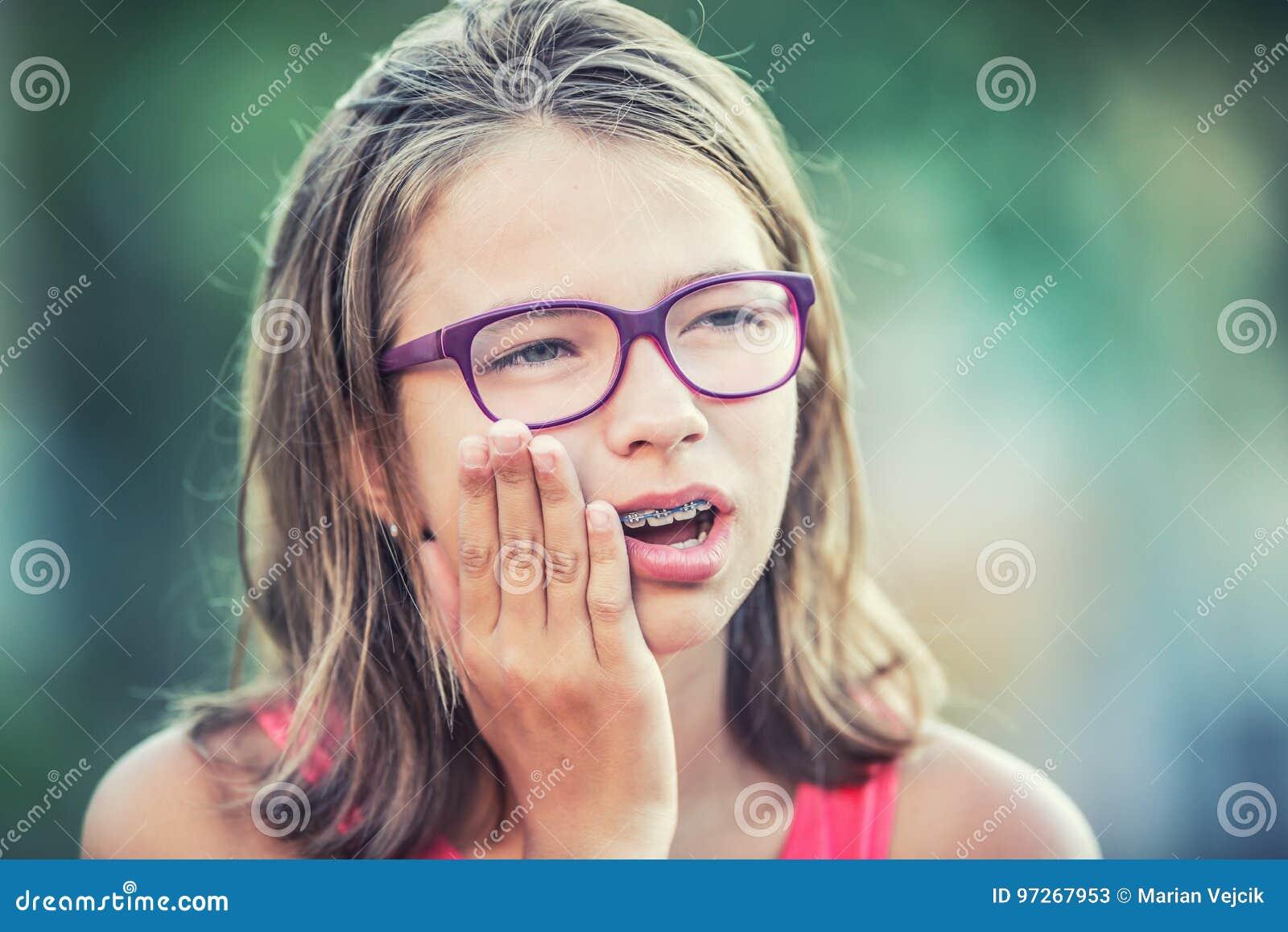 Πορτρέτο του νέου κοριτσιού εφήβων με τον πονόδοντο Κορίτσι με τα οδοντικά στηρίγματα και τα γυαλιά
