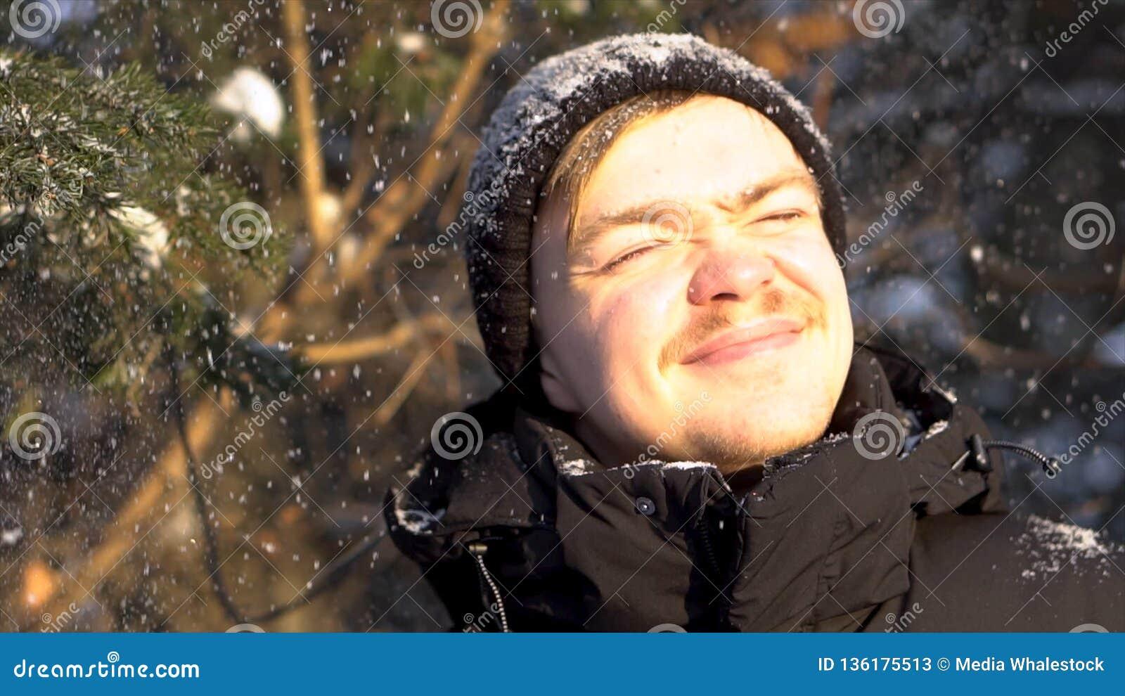 Πορτρέτο του νέου, χαμογελώντας ατόμου με το moustache που απολαμβάνει τις χιονοπτώσεις στο χειμερινό δάσος, που στραβίζει τα μάτ