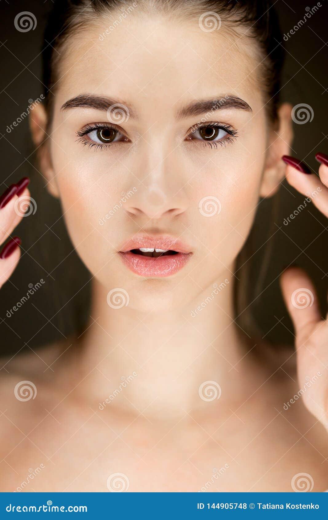 Πορτρέτο του νέου όμορφου καφετής-μαλλιαρού κοριτσιού με το φυσικό makeu