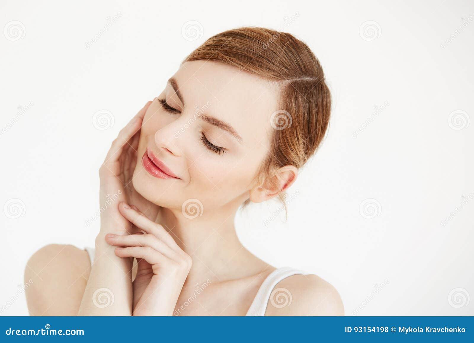 Πορτρέτο του νέου όμορφου χαμόγελου κοριτσιών με τις ιδιαίτερες προσοχές σχετικά με το πρόσωπο πέρα από το άσπρο υπόβαθρο Του προ