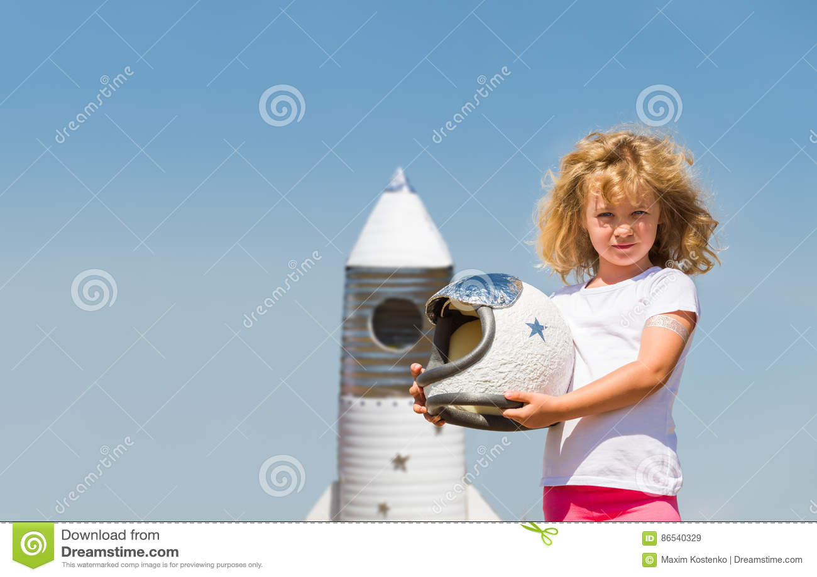 Πορτρέτο του ξανθού μικρού κοριτσιού σε ένα κοστούμι αστροναυτών με τον πύραυλο παιχνιδιών που ονειρεύεται να γίνει spacemen