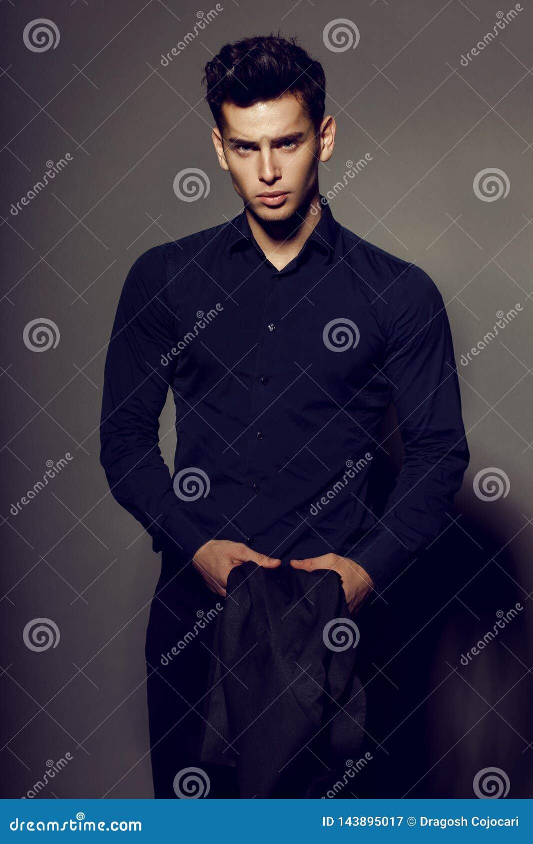 Πορτρέτο του πλούσιου, προκλητικού ατόμου brunette στη μαύρη τοποθέτηση κοστουμιών στη κάμερα, που απομονώνεται στο γκρίζο υπόβαθ