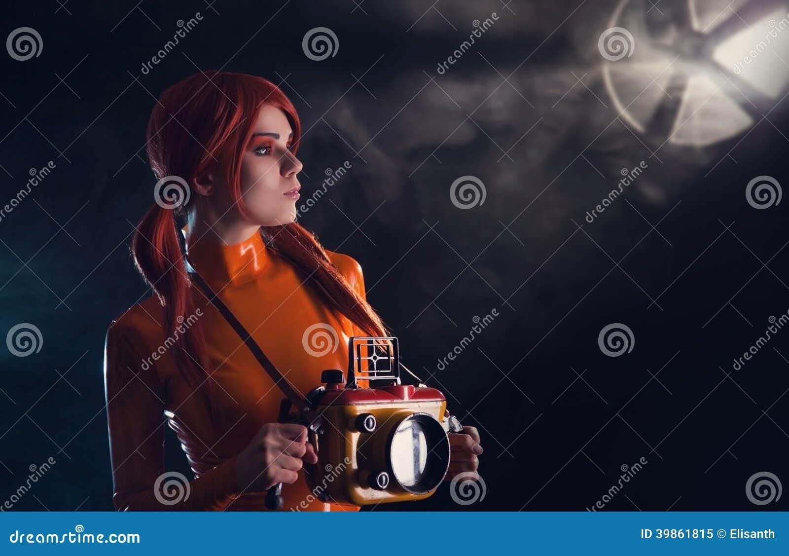 Πορτρέτο του προκλητικού κοριτσιού αστροναυτών στο πορτοκαλί ασβέστιο λατέξ