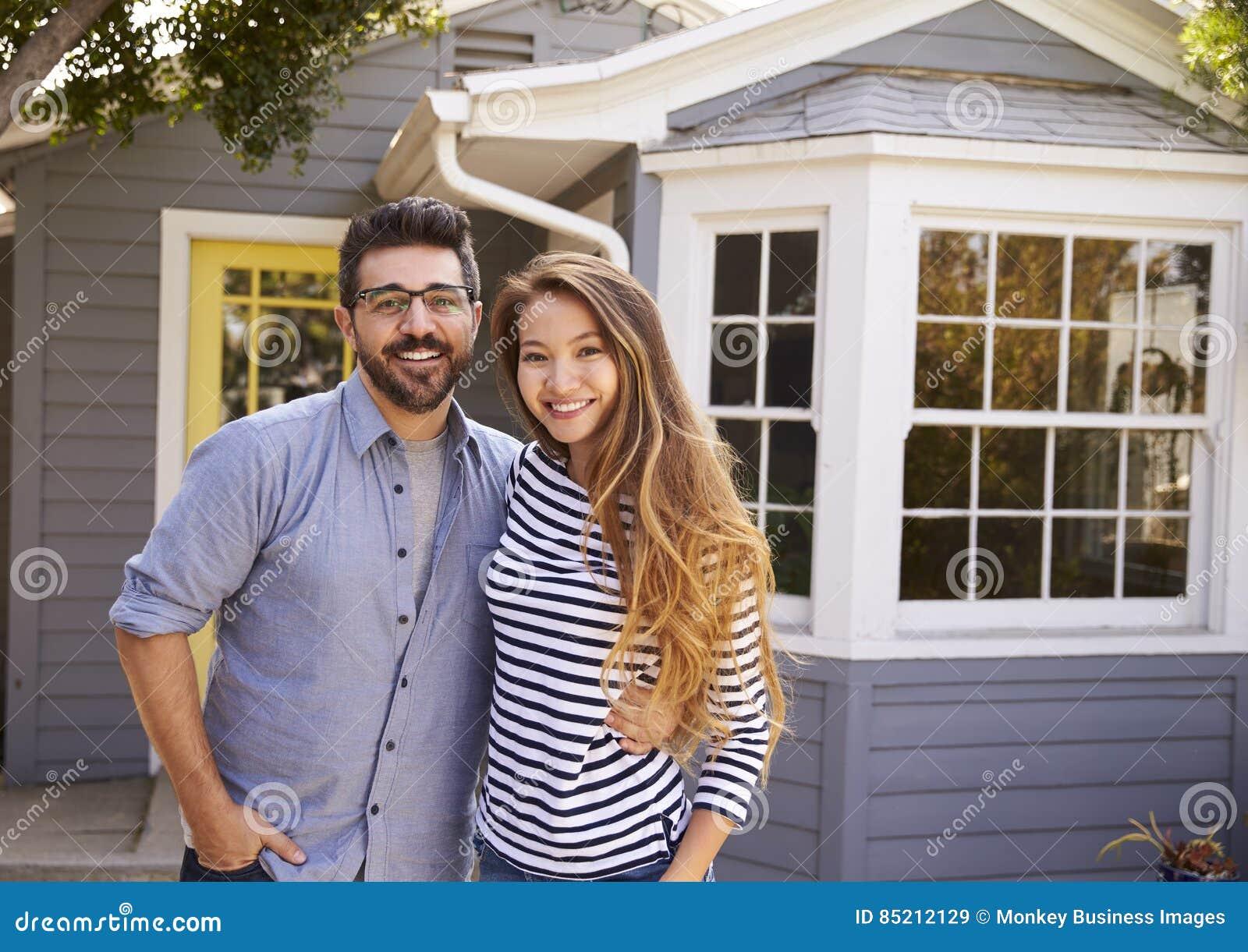 Πορτρέτο του συγκινημένου ζεύγους που στέκεται έξω από το νέο σπίτι