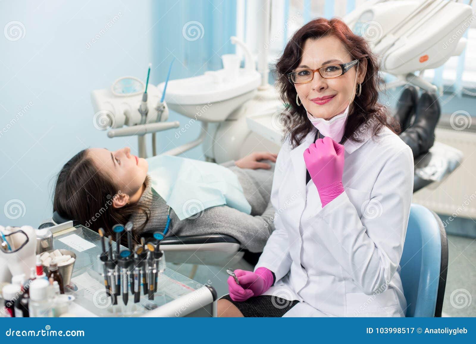 Πορτρέτο του φιλικού θηλυκού οδοντιάτρου υπό την προεδρία του ασθενή στο οδοντικό γραφείο