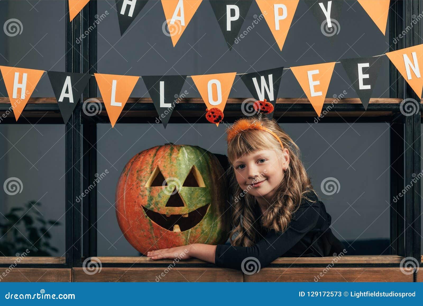 πορτρέτο του χαμογελώντας παιδιού στο κοστούμι αποκριών στη χαρασμένη κολοκύθα και τις κρεμώντας σημαίες