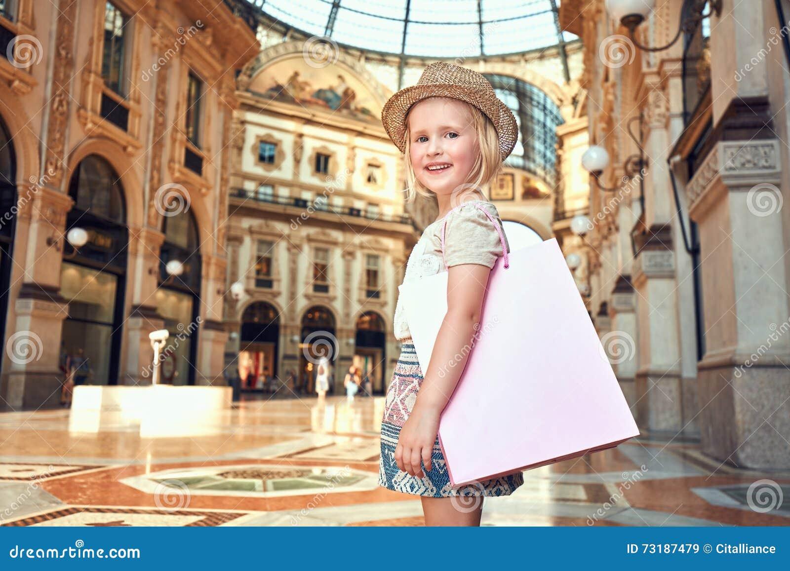 Πορτρέτο του χαμογελώντας κοριτσιού μόδας με την τσάντα αγορών σε Galleria