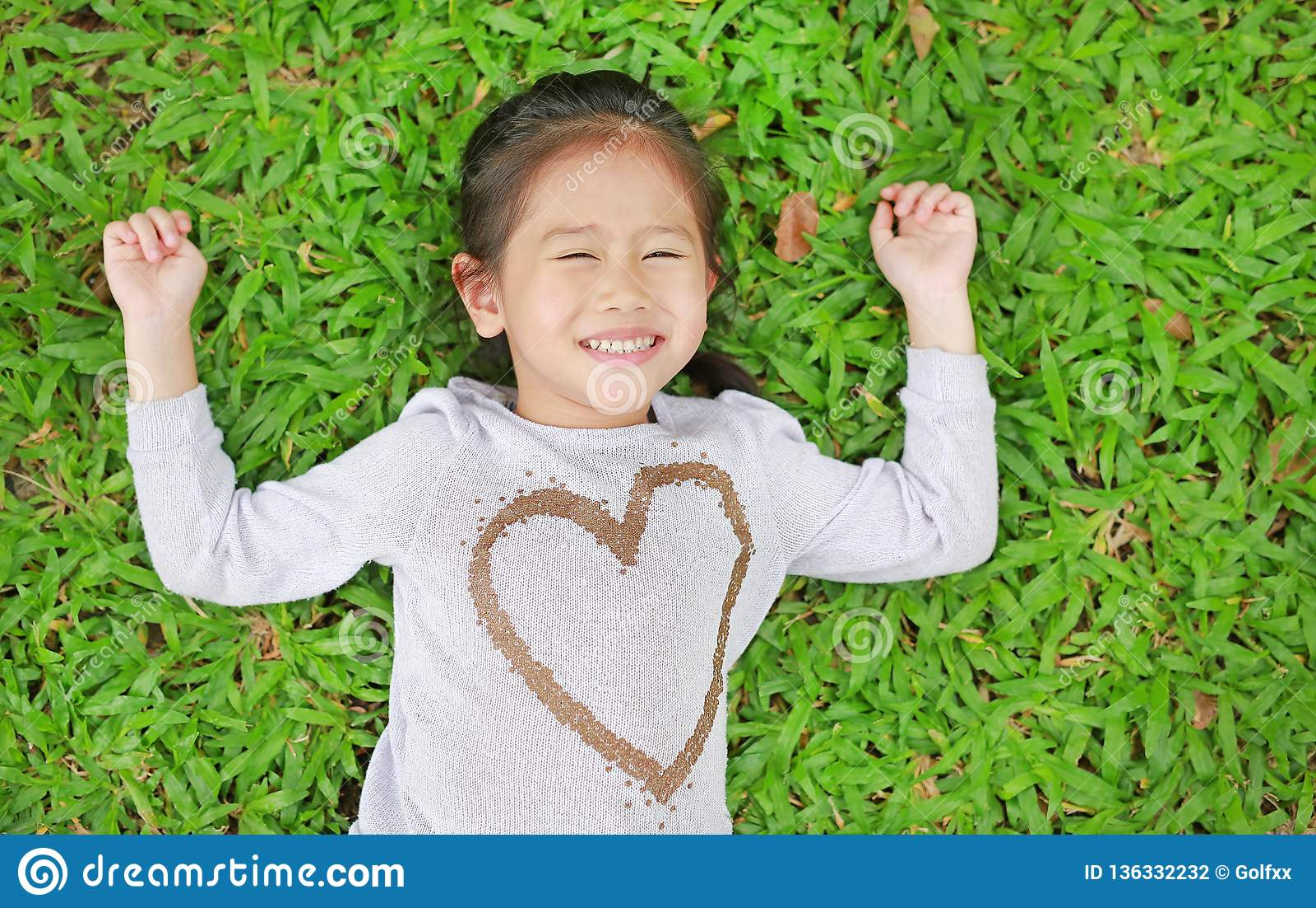 Πορτρέτο του χαμόγελου χαριτωμένο λίγου ασιατικού κοριτσιού παιδιών που βρίσκεται στον πράσινο χορτοτάπητα