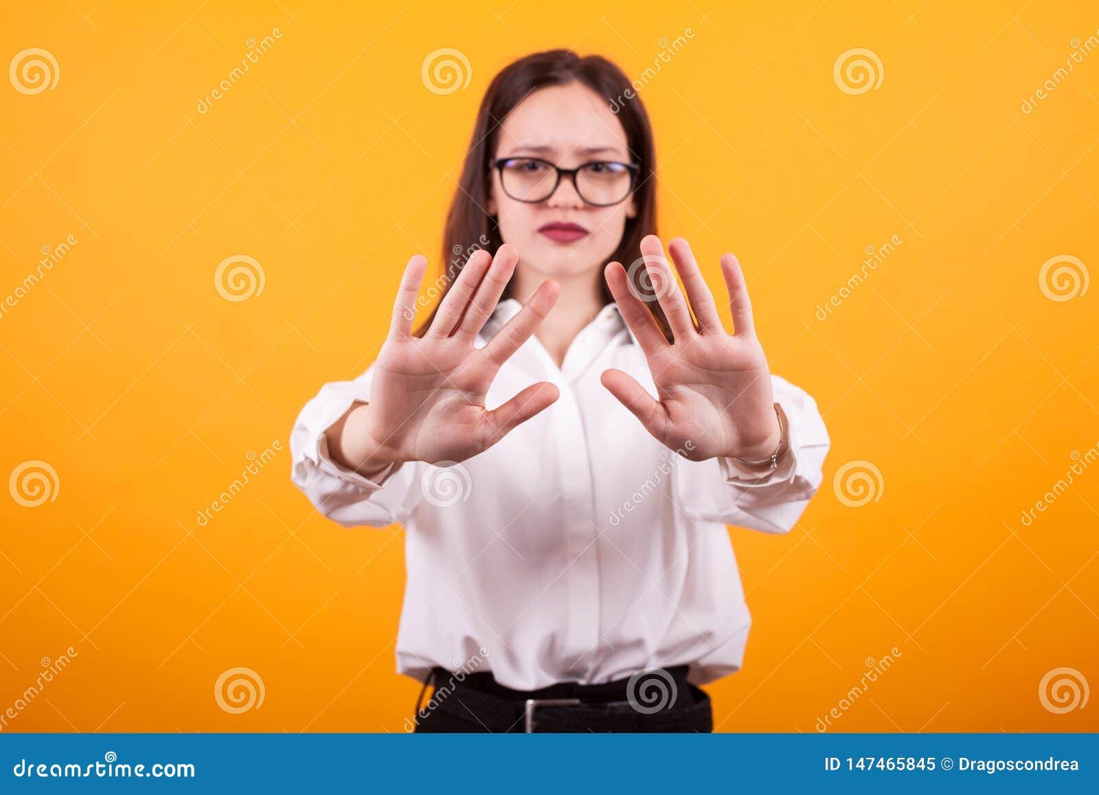 Πορτρέτο του χαριτωμένου κοριτσιού που παρουσιάζει χέρια στη κάμερα στο στούντιο πέρα από το κίτρινο υπόβαθρο