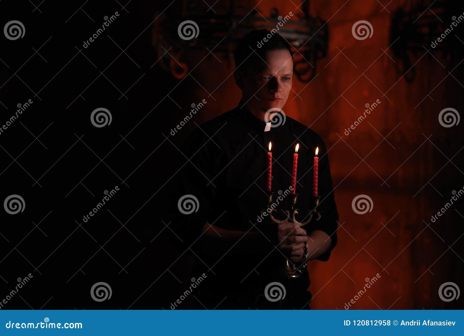Πορτρέτο του όμορφου καθολικού παπά ή του πάστορα με το περιλαίμιο σκυλιών, σκούρο κόκκινο υπόβαθρο με το κόκκινο κερί τρία στο χ