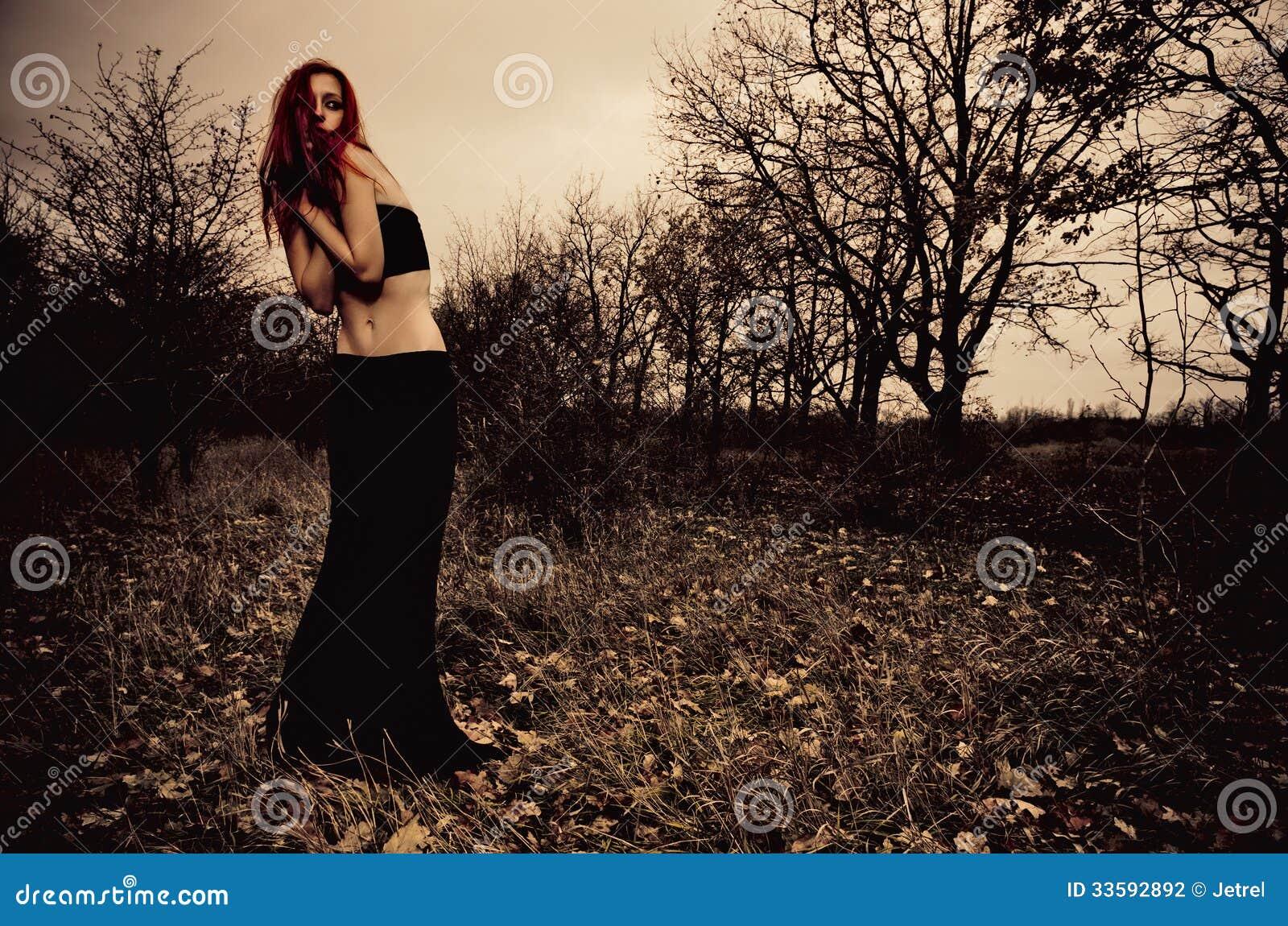Πορτρέτο του όμορφου λυπημένου κοριτσιού μεταξύ των δέντρων φθινοπώρου