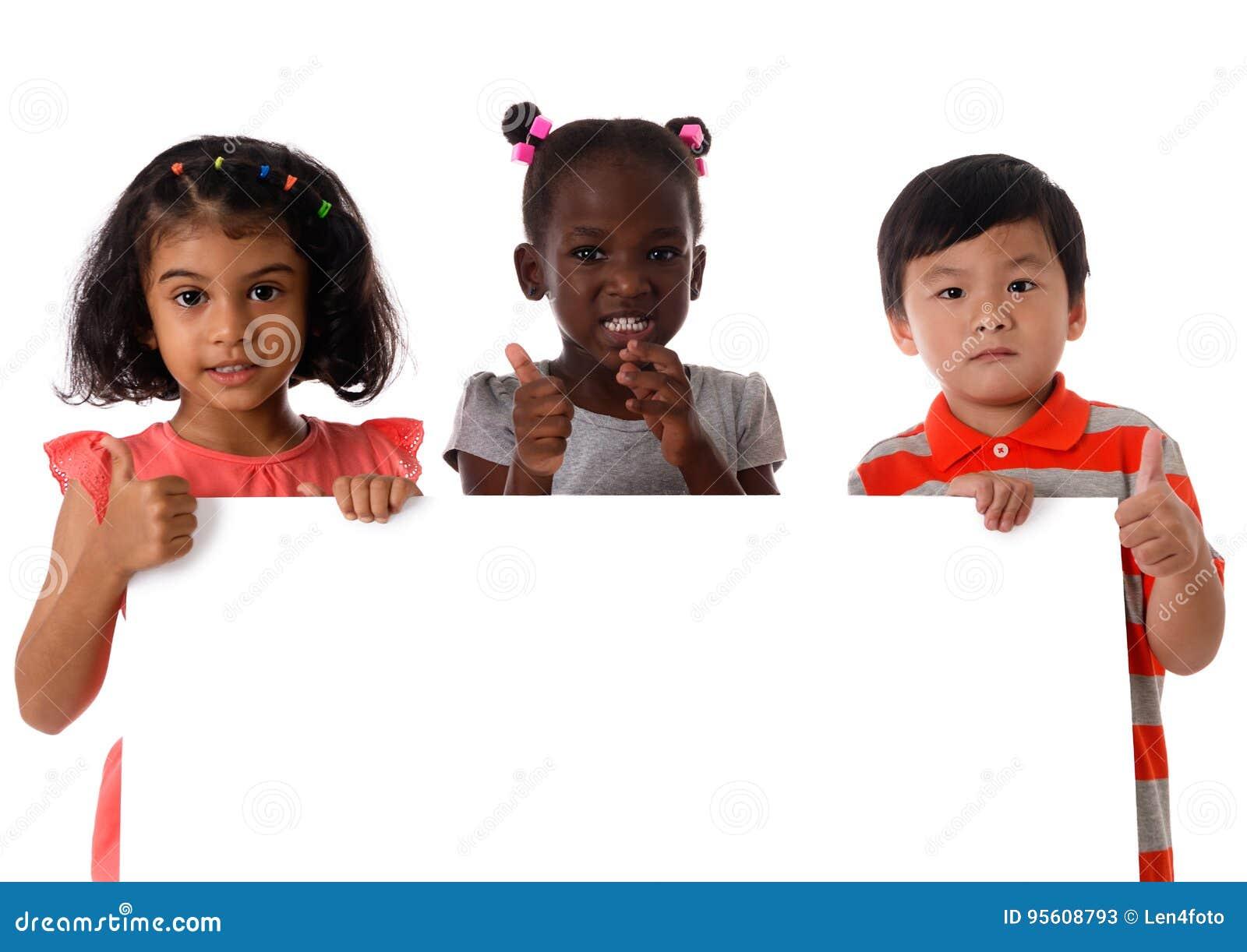 Πορτρέτο τρία των πολυφυλετικών παιδιών στο στούντιο με το λευκό πίνακα απομονωμένος