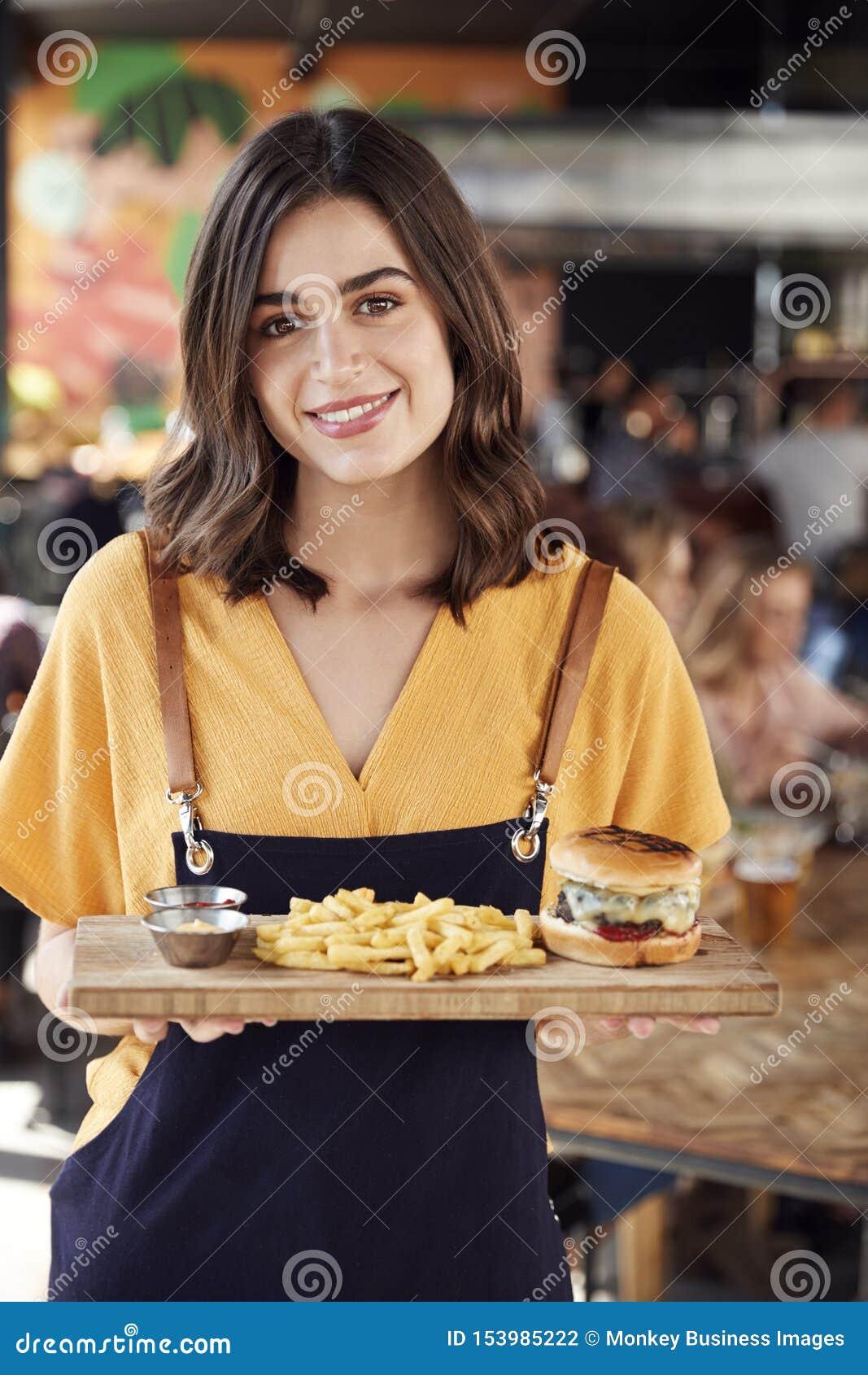 Πορτρέτο των εξυπηρετώντας τροφίμων σερβιτορών στους πελάτες στο πολυάσχολο εστιατόριο φραγμών