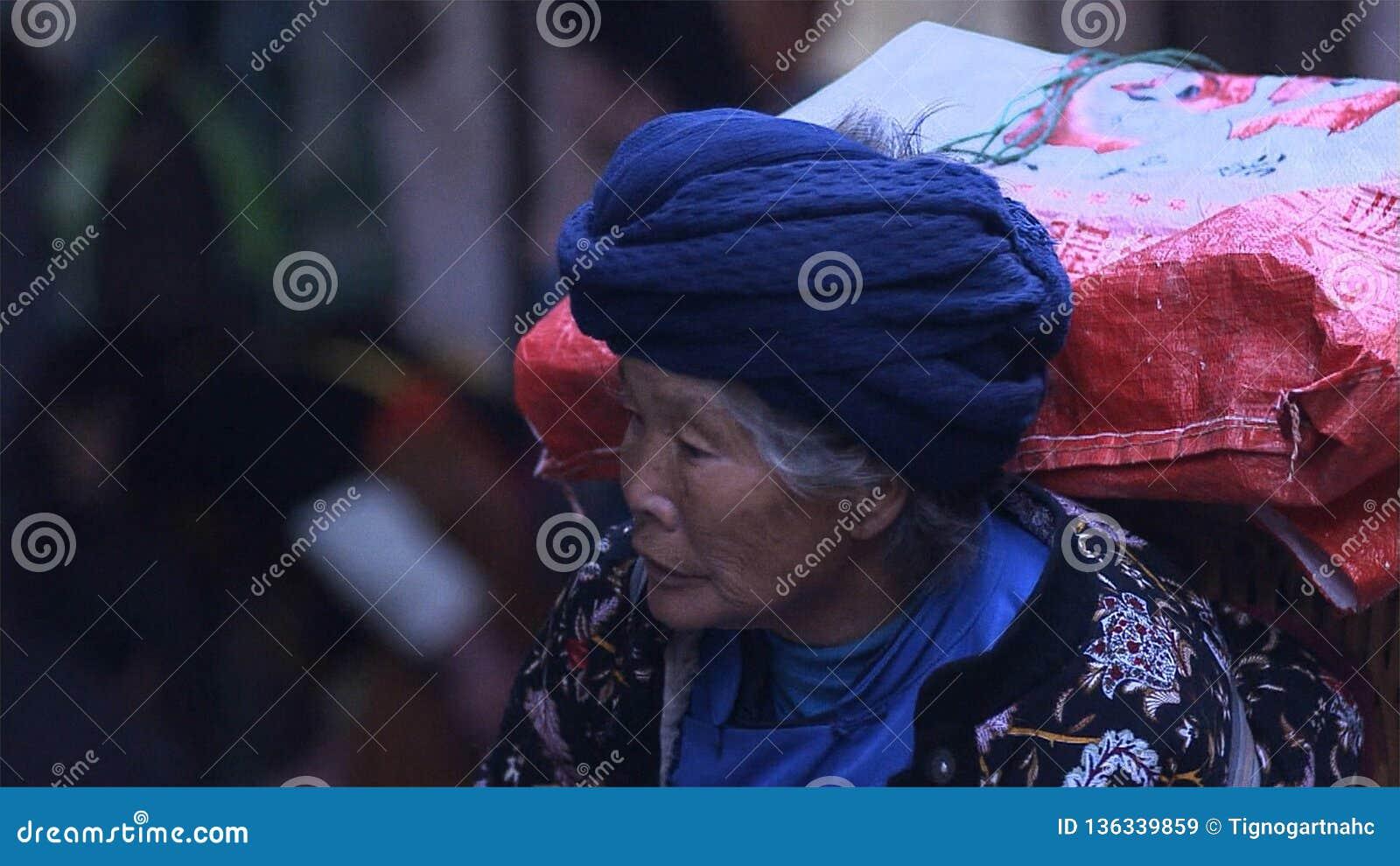 Πορτρέτο των ηλικιωμένων κινεζικών γυναικών που φέρνουν την επαρχία τσαντών yunnan Κίνα