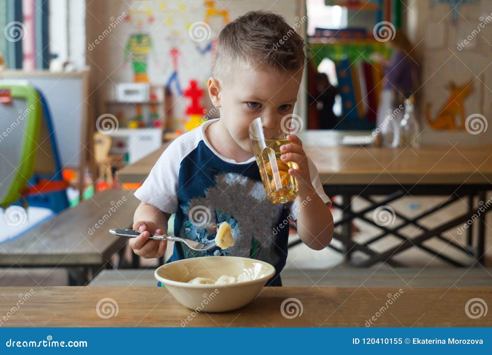 Πορτρέτο χαριτωμένου λίγος καυκάσιος χρονών χυμός φρούτων κατανάλωσης παιδιών αγοριών μικρών παιδιών 3 σε ένα γυαλί, συνεδρίαση α