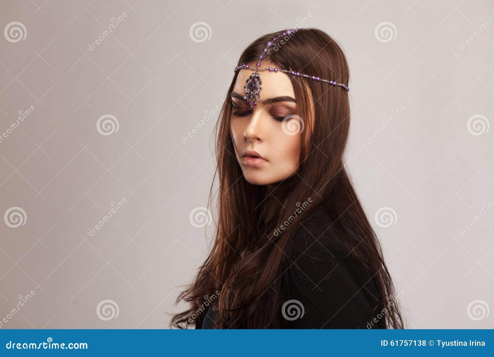 Πορτρέτο ύφους μόδας της όμορφης γυναίκας brunette με την τρίχα ornam
