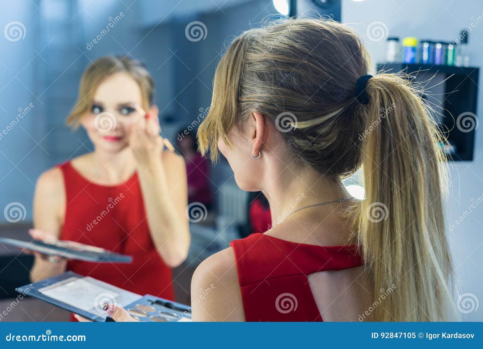 Πορτρέτο Fashio του όμορφου νέου κοριτσιού που κάνει τη σύνθεση κοντά στον καθρέφτη
