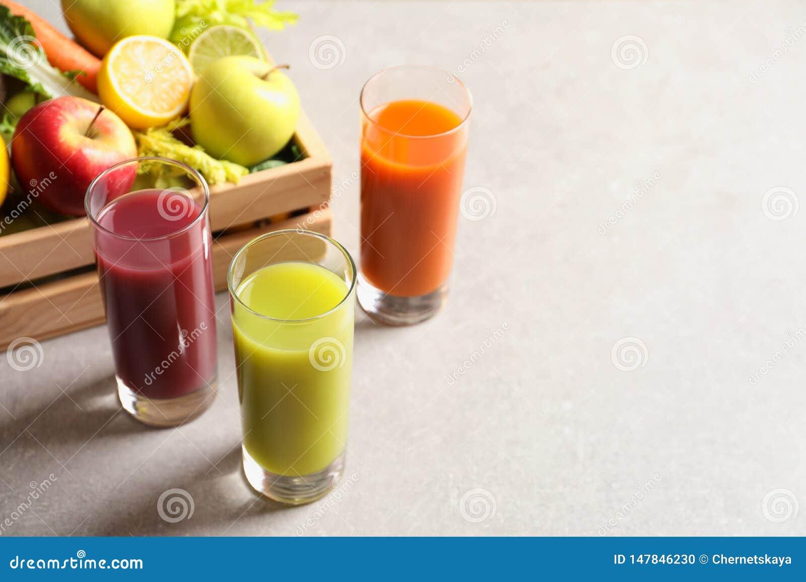 Ποτήρια των διαφορετικών χυμών και του ξύλινου κλουβιού με τα φρέσκα συστατικά στον πίνακα