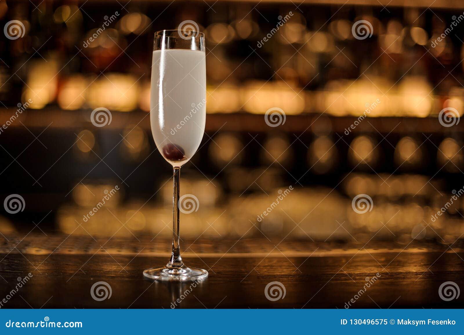 Ποτήρι ενός γαλλικού κοκτέιλ 75 με το μούρο που στέκεται στο cou φραγμών