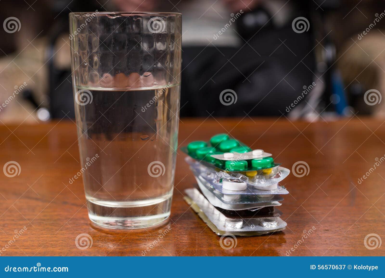 Download Ποτήρι του νερού στον πίνακα εκτός από το σωρό των χαπιών Στοκ Εικόνα - εικόνα από σωρός, γυαλί: 56570637