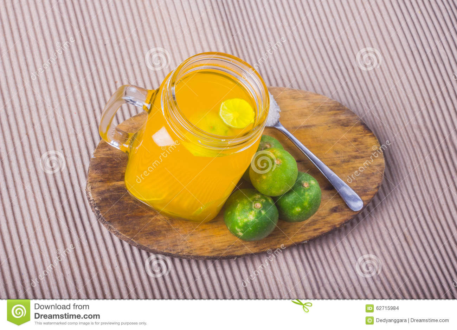 Ποτήρι του χυμού από πορτοκάλι με το άχυρο και των φετών στον ξύλινο πίνακα