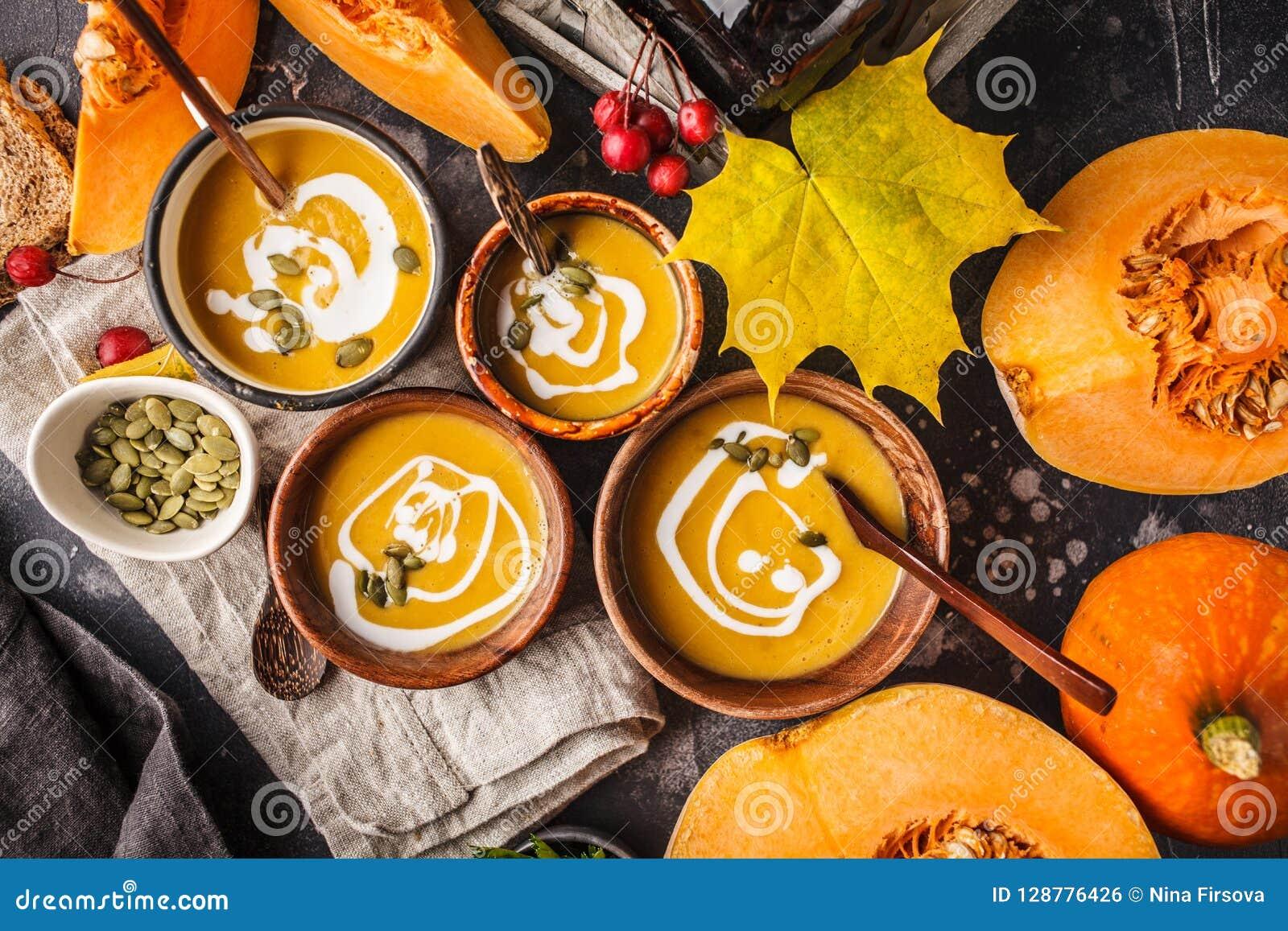 Πουρές σούπας κολοκύθας φθινοπώρου με την κρέμα στα φλυτζάνια, το τοπίο φθινοπώρου