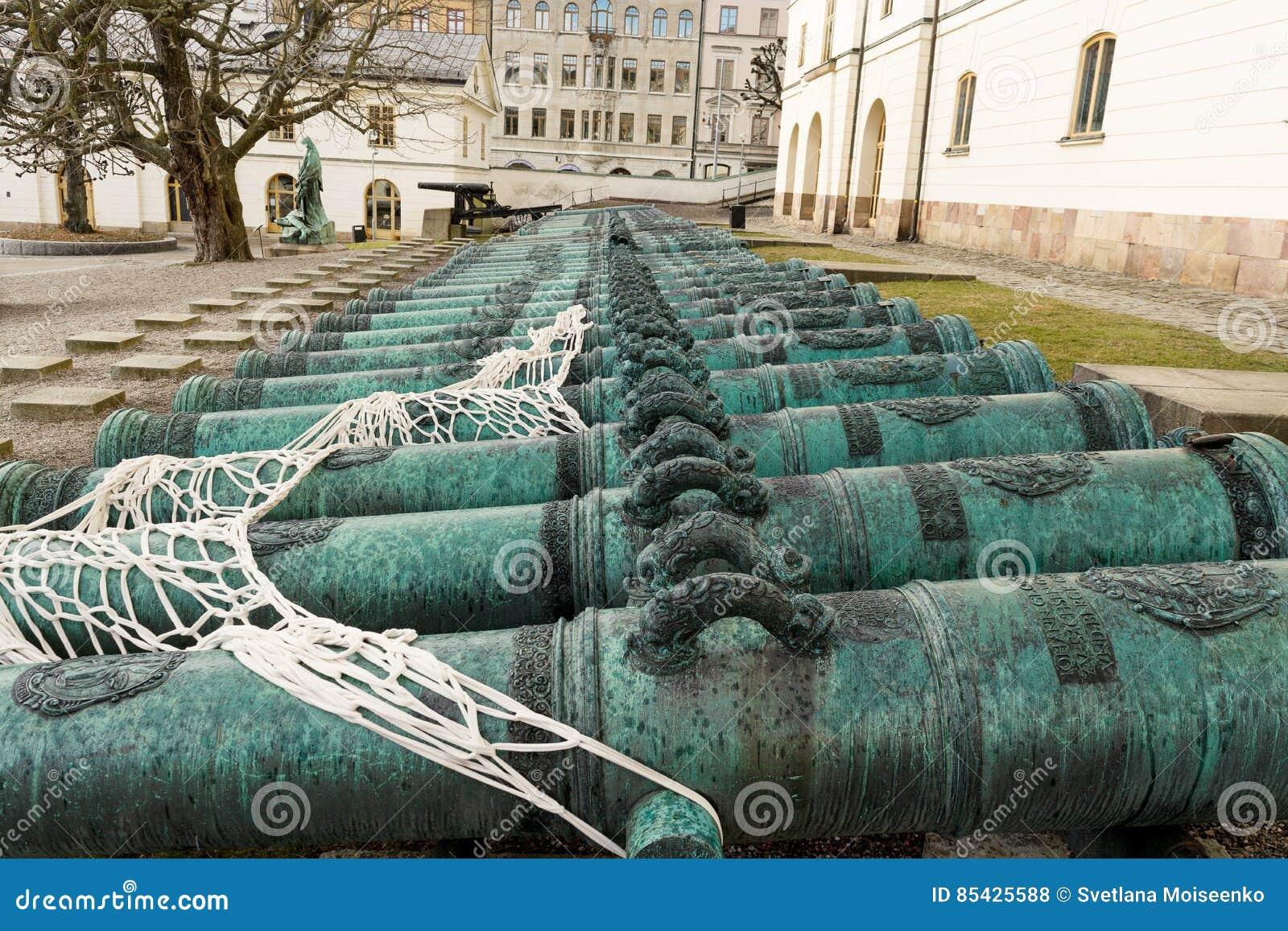 Πολλά αρχαία πυροβόλα πυροβολικού μετάλλων κατά μήκος του τοίχου