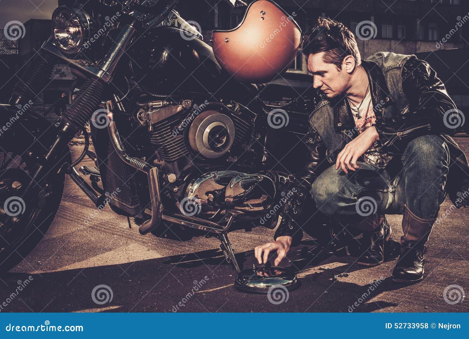 Ποδηλάτης και η μοτοσικλέτα ύφους bobber του